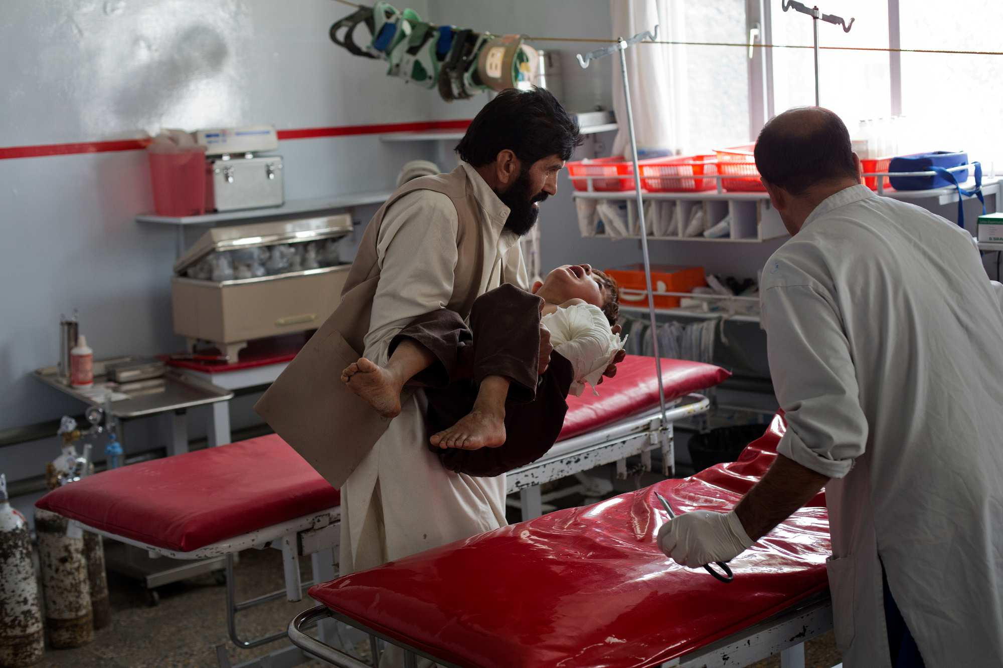 Noor Pacha carries his son, Noorullah, 7, into the Outpatient Department at Emergency Hospital. Noorullah was in their home in Pirkuti, Paktika province, when the Afghanistan National Security Forces engaged the Taliban in a firefight, around 6 o'clock in the evening. A blast sent shrapnel through the window, and hit Noorullah in the arm and back.