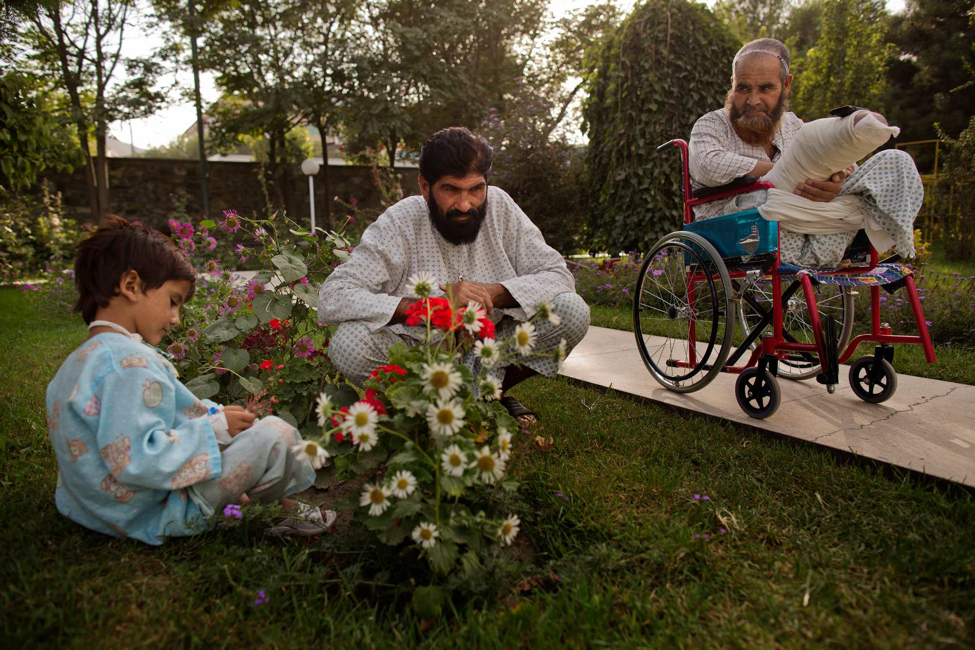 Noor Pacha, center, sits in the garden with his injured son, Noorullah, 7, left, as fellow patient Ab Ahad, 45, looks on.