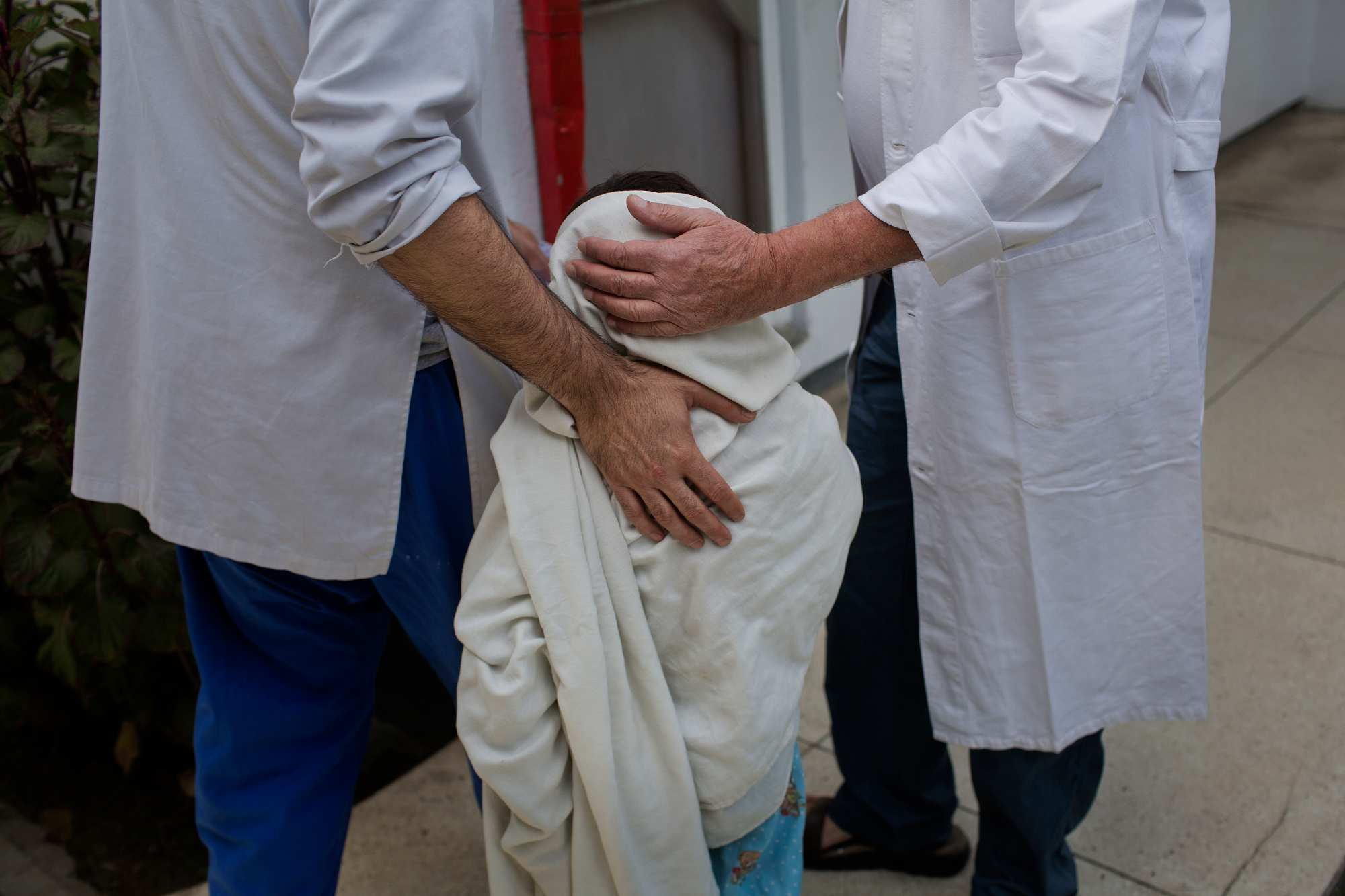 Physical therapist Alberto Carreno, left, and Dr. Alberto Landini, right, comfort Sangeer, 7, at Emergency Surgical Center. Sangeer was upset on visiting day because his family was unable to make the trip to Kabul to visit him.