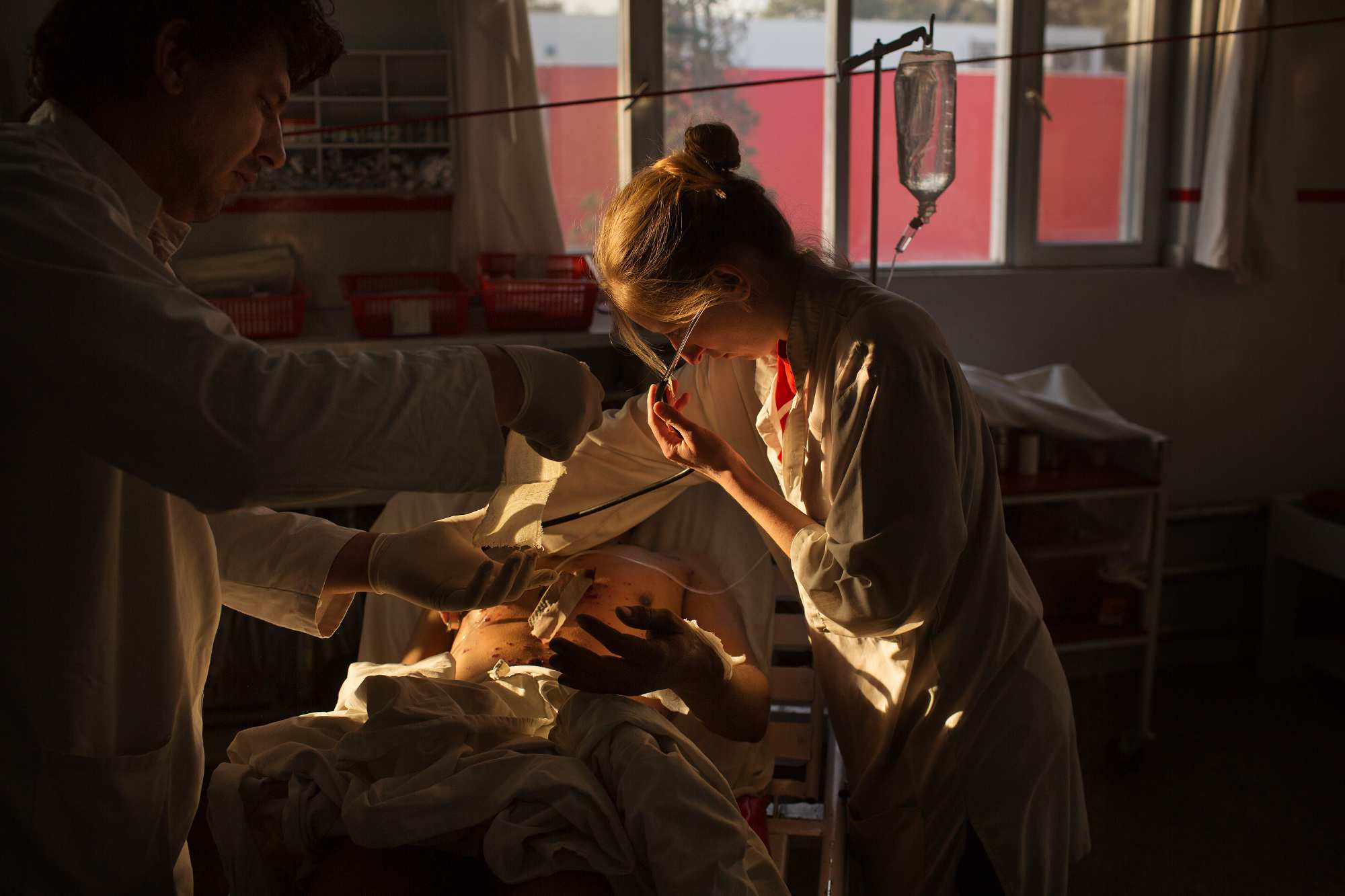 Nurse Claire Hayzelden, center, examines Jamat Gul, 28, who suffered shrapnel injuries in an IED blast, in the emergency room at Emergency Surgical Center.