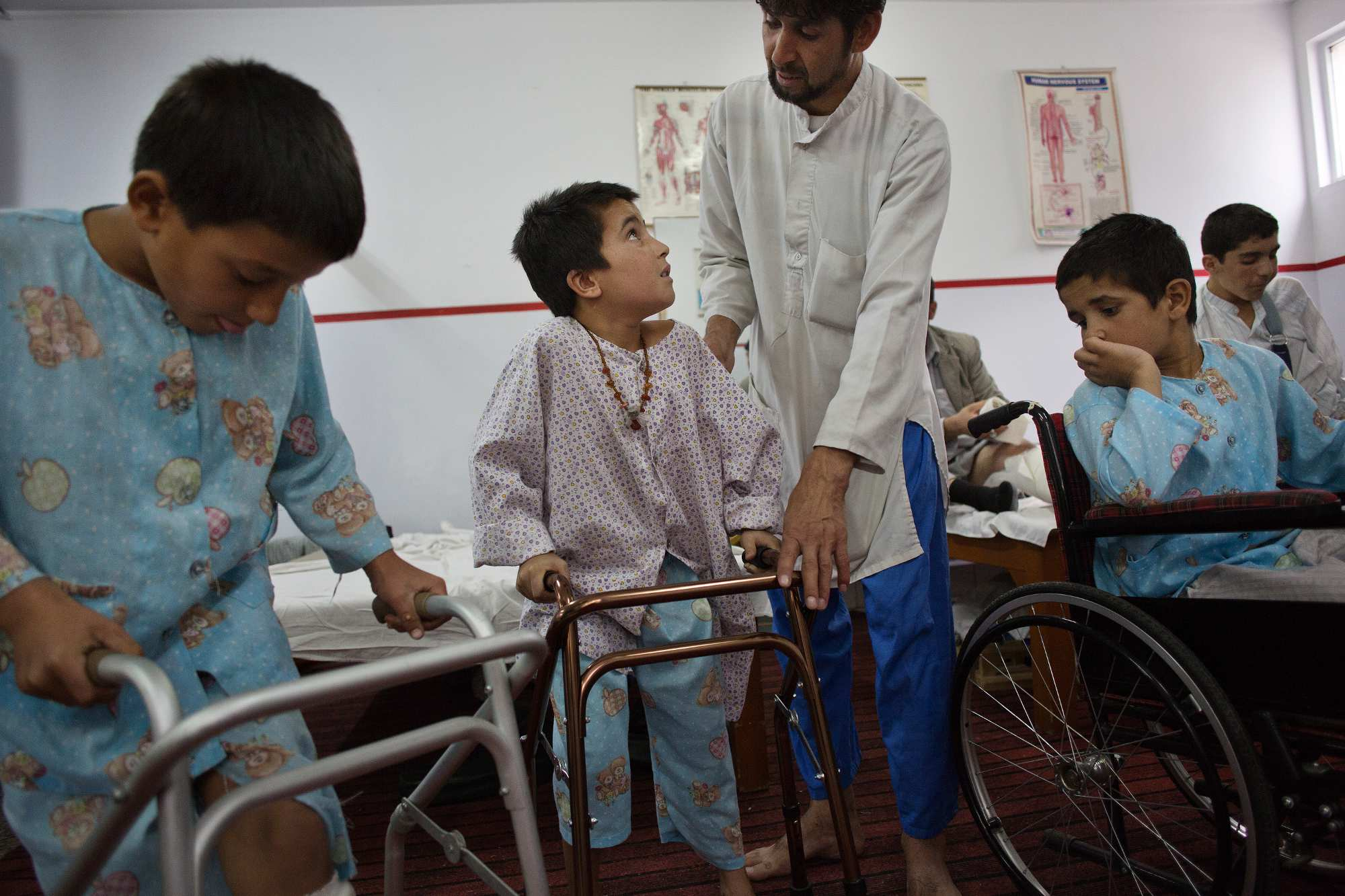 Physiotherapist Yusef, center, helps Ismael Jan, 6, center, try to walk as Rahmatullah, left, tries out a walker and Hakim Jan, 10, right, looks on, in the physical therapy department. All three boys suffered traumatic injuries to their legs in the fighting in their home districts and were treated at Emergency.
