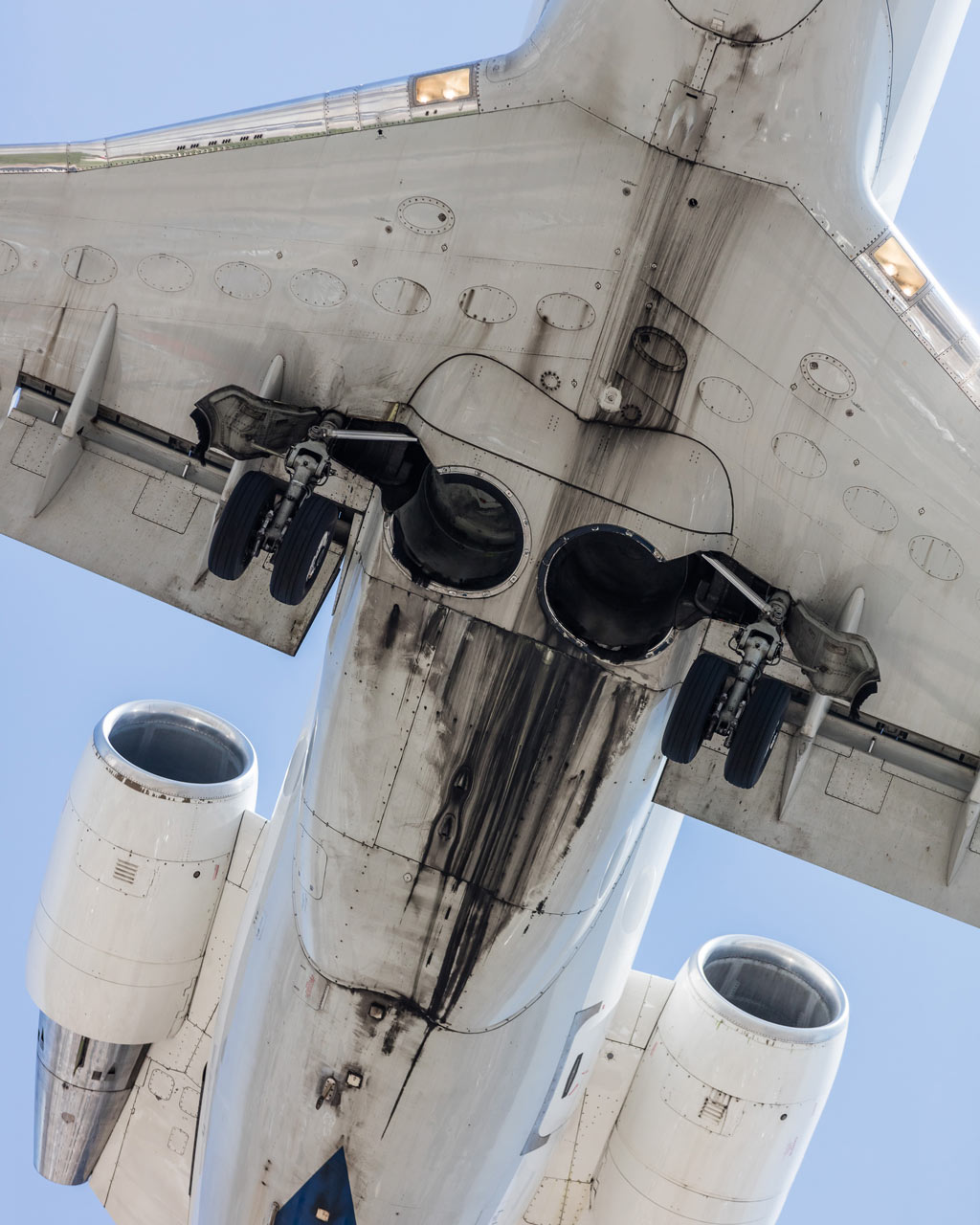 A regional jet approaches LAX airport and displays oil, grease, and dirt accumulated on the bottom of the fuselage.