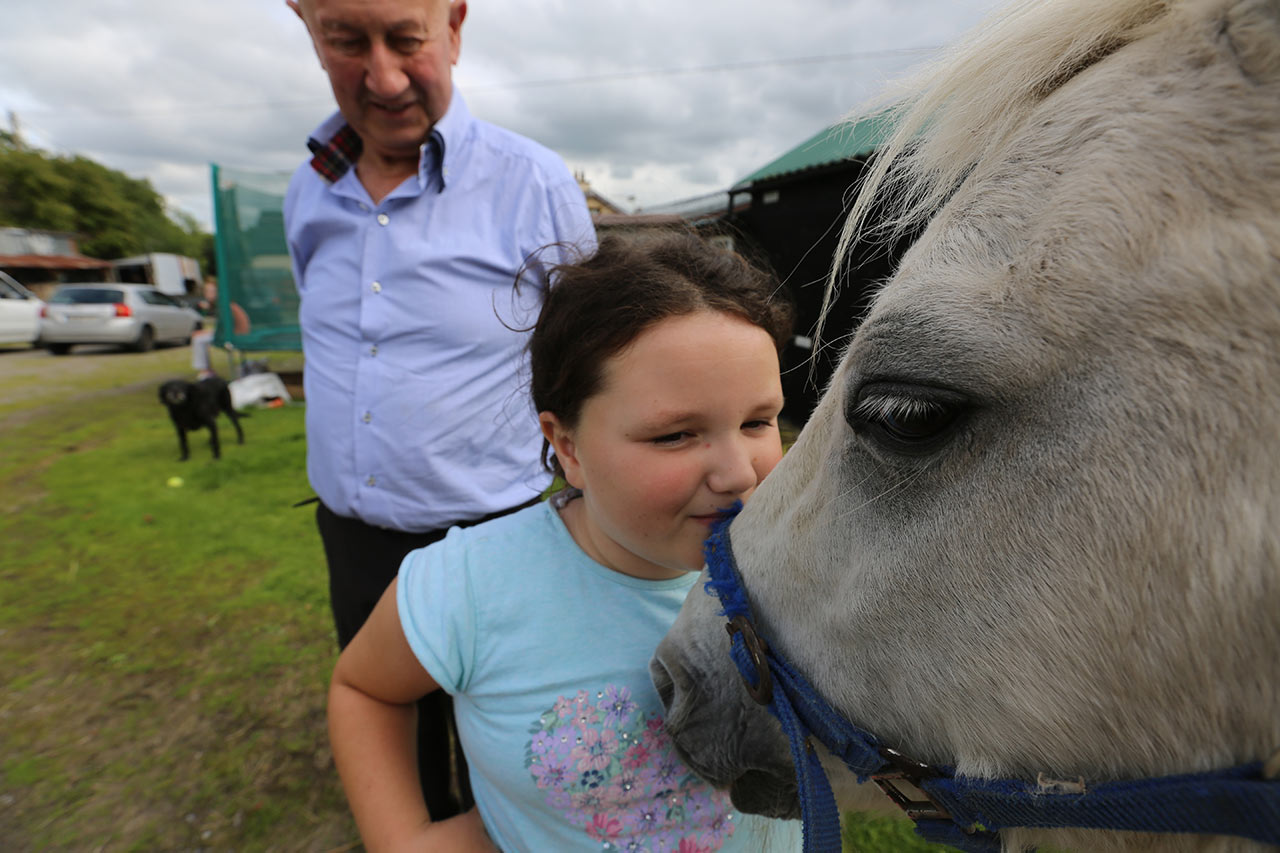 Anthony O'Reilly watches as his granddaughter plays with the farm pony in the town of Belturbet in the Irish Republic.