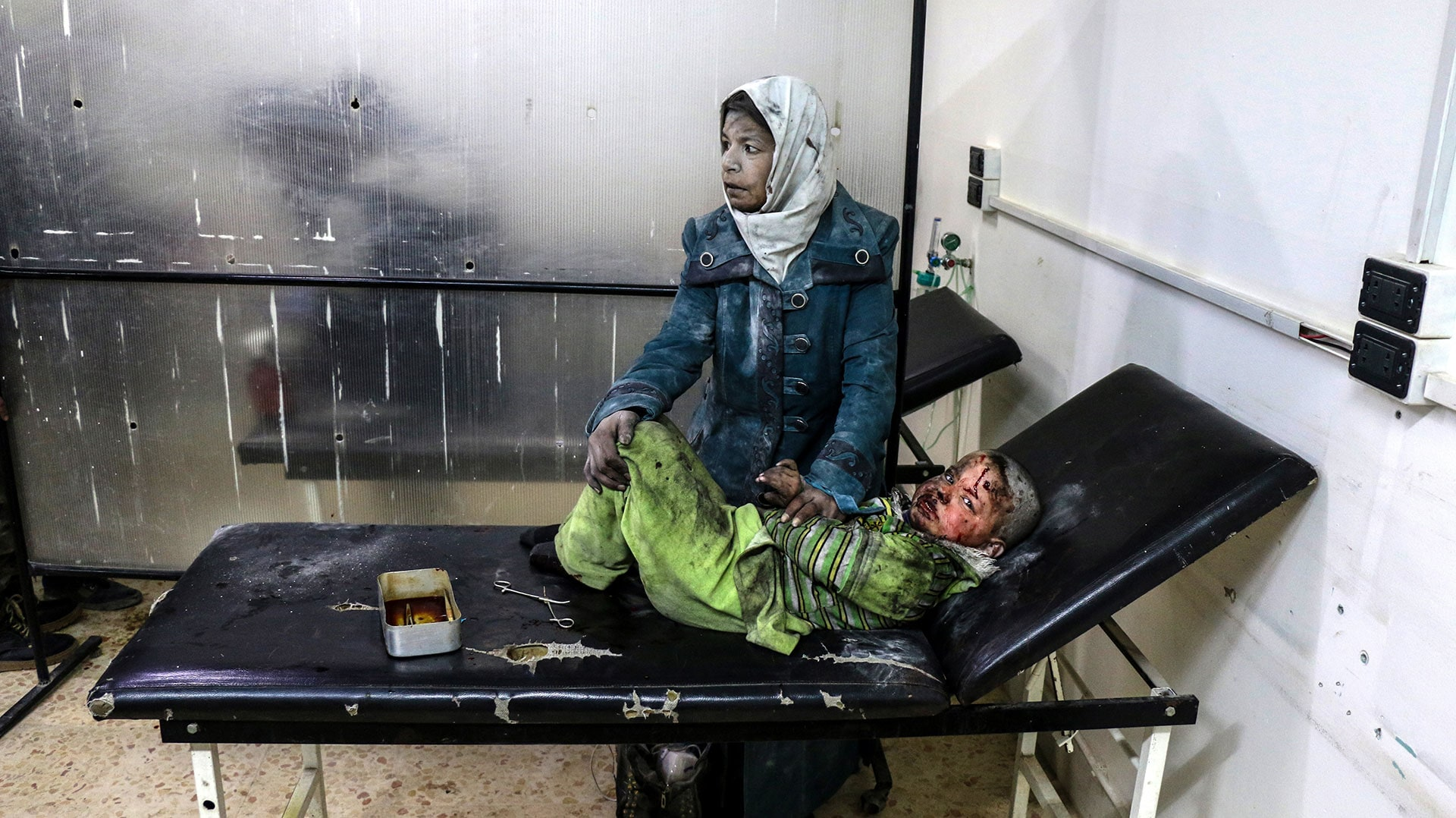 An injured woman comforts a child at a hospital