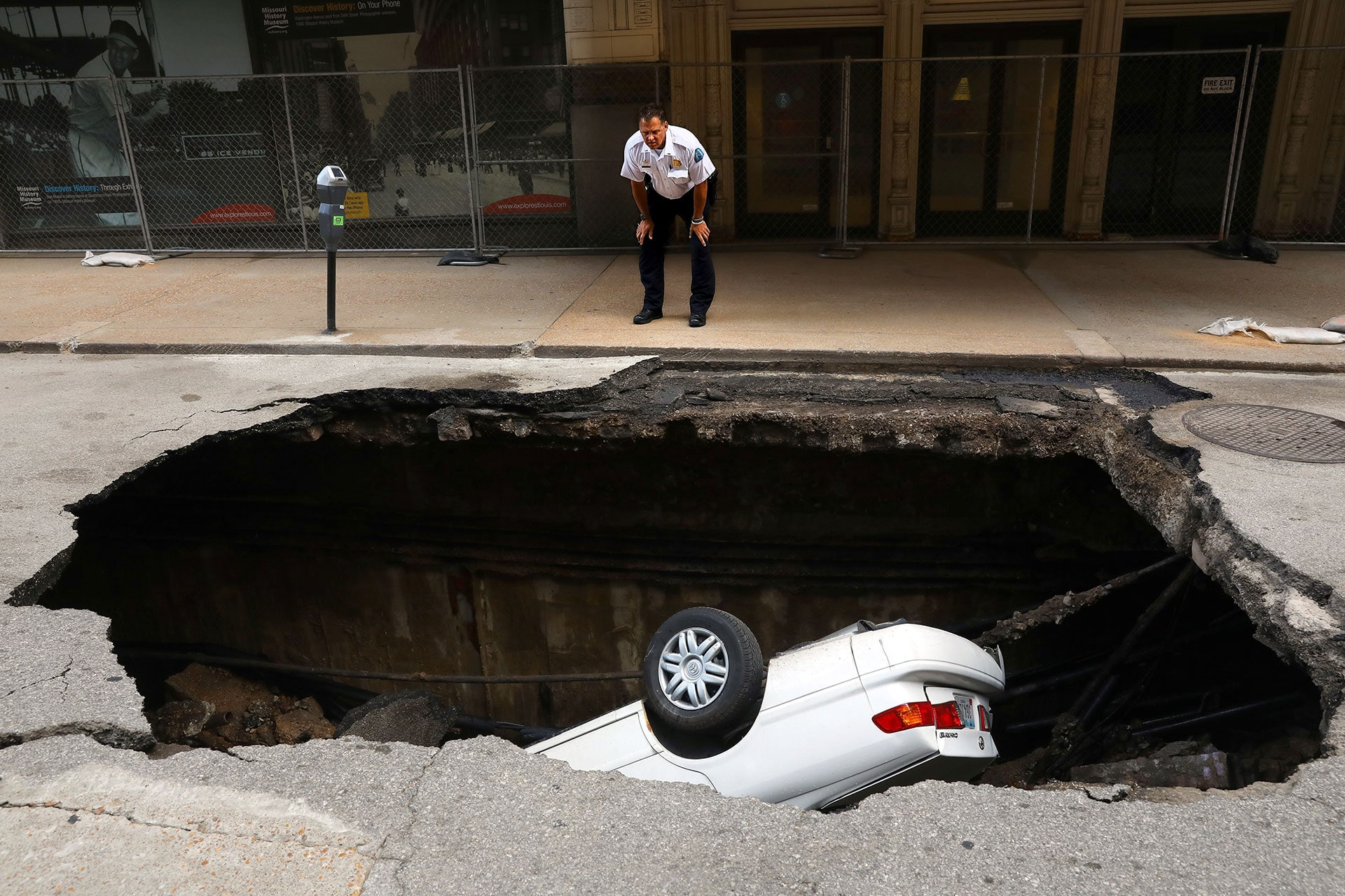 A police officer looks over a large sinkhole