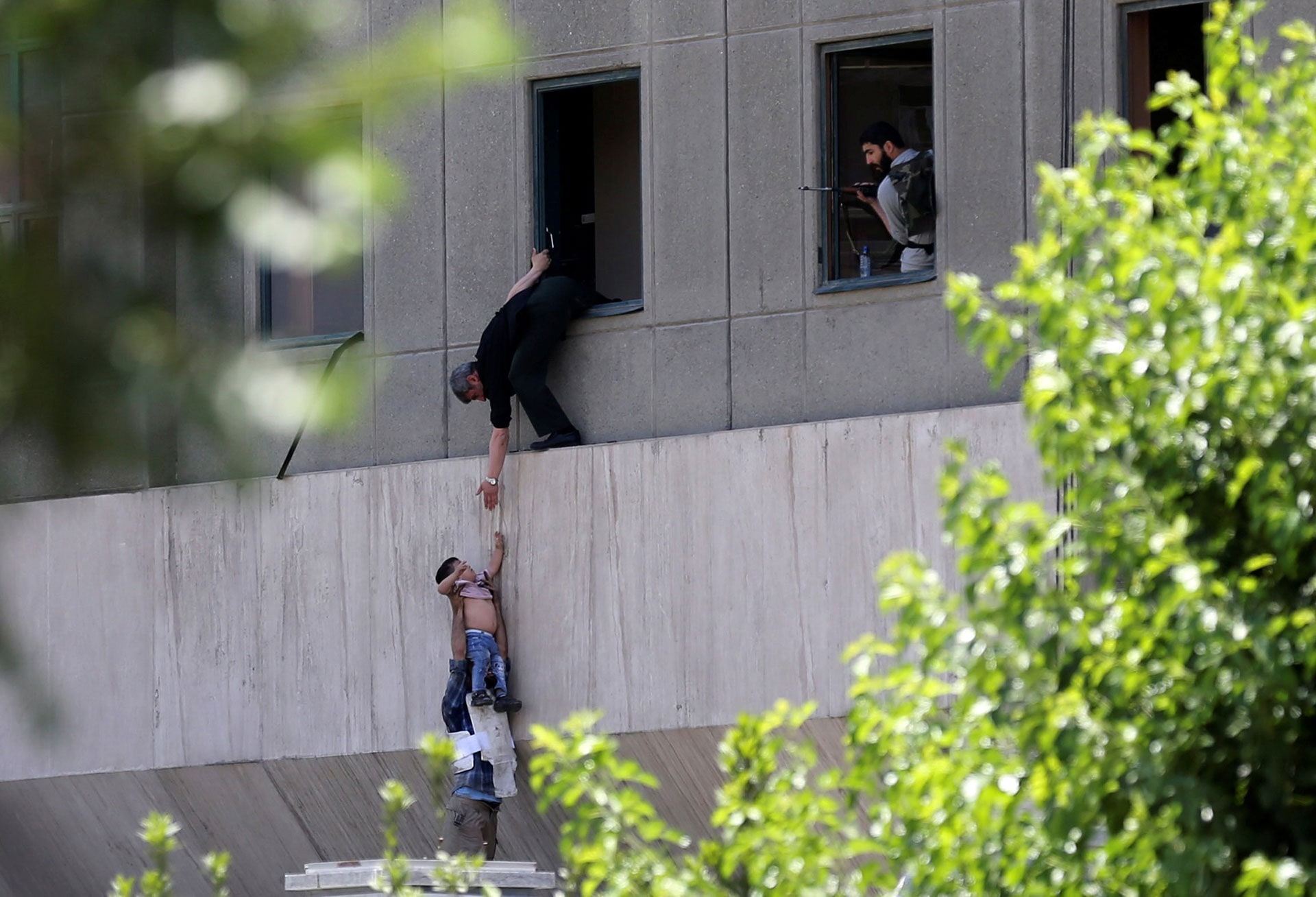 A boy is evacuated during an attack on the Iranian Parliament