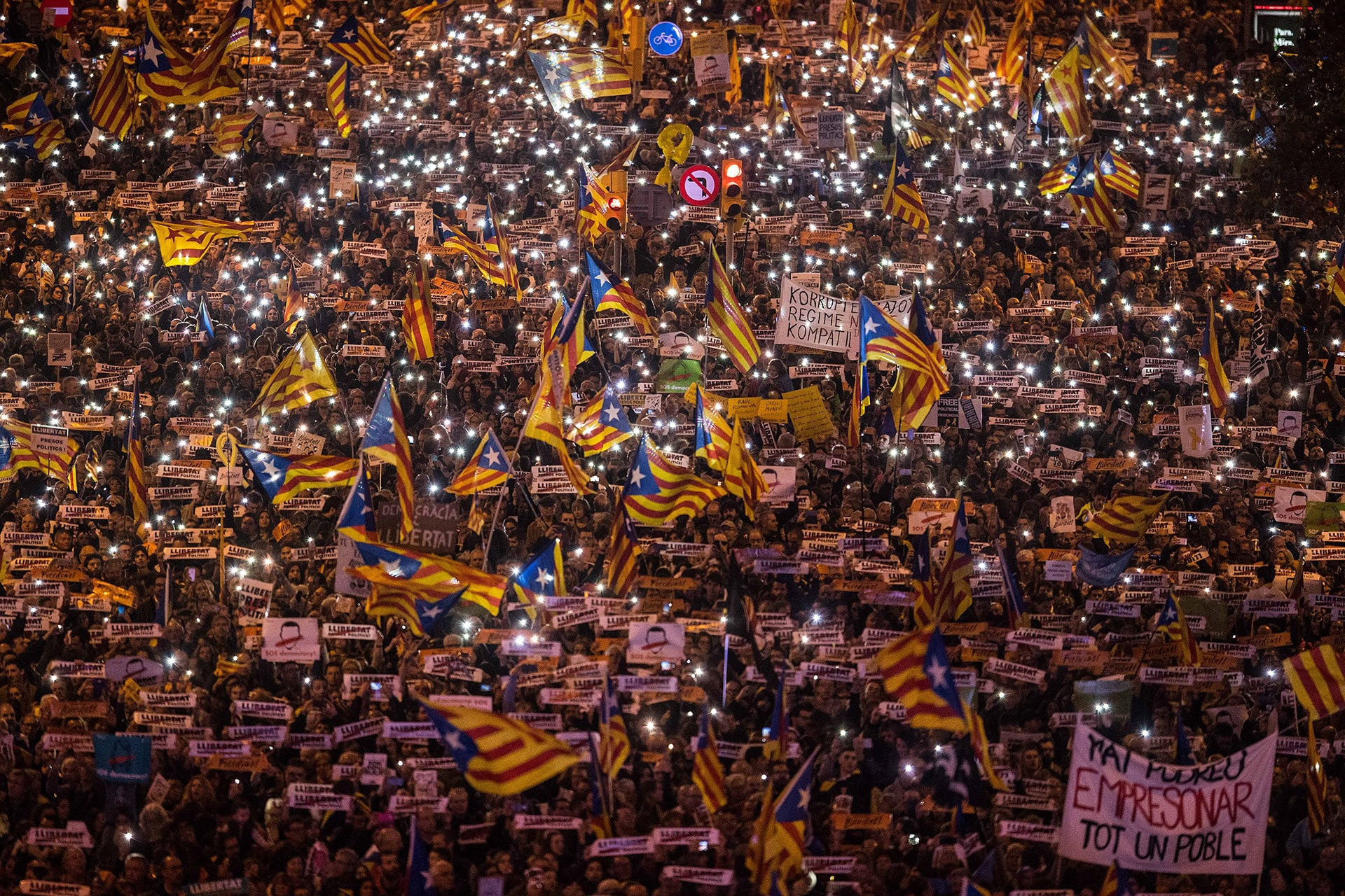 Protesters hold their phones up during a pro-independence demonstration