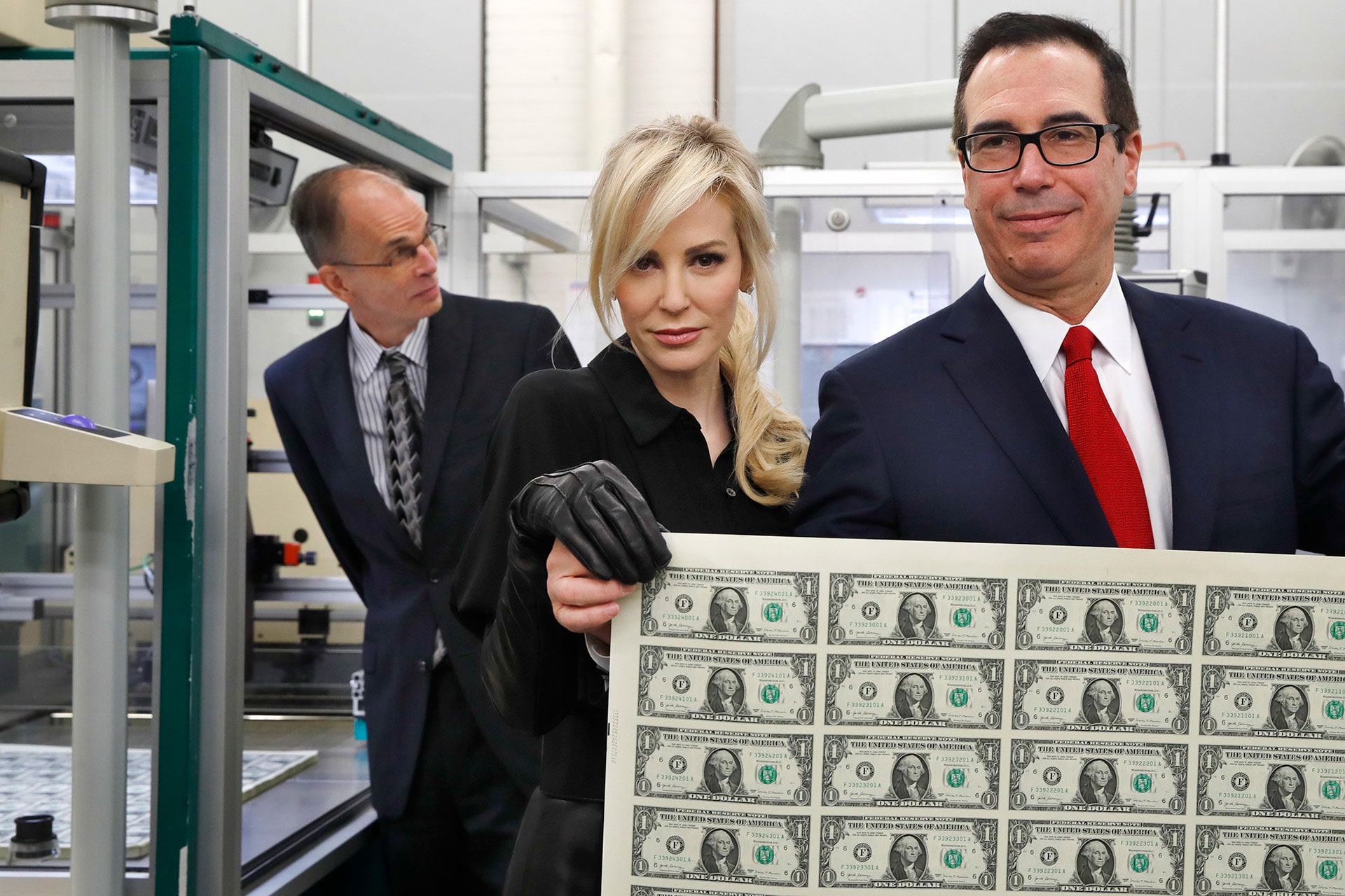 Treasury Secretary Steven Mnuchin and his wife, Louise Linton, hold up a sheet of new $1 bills