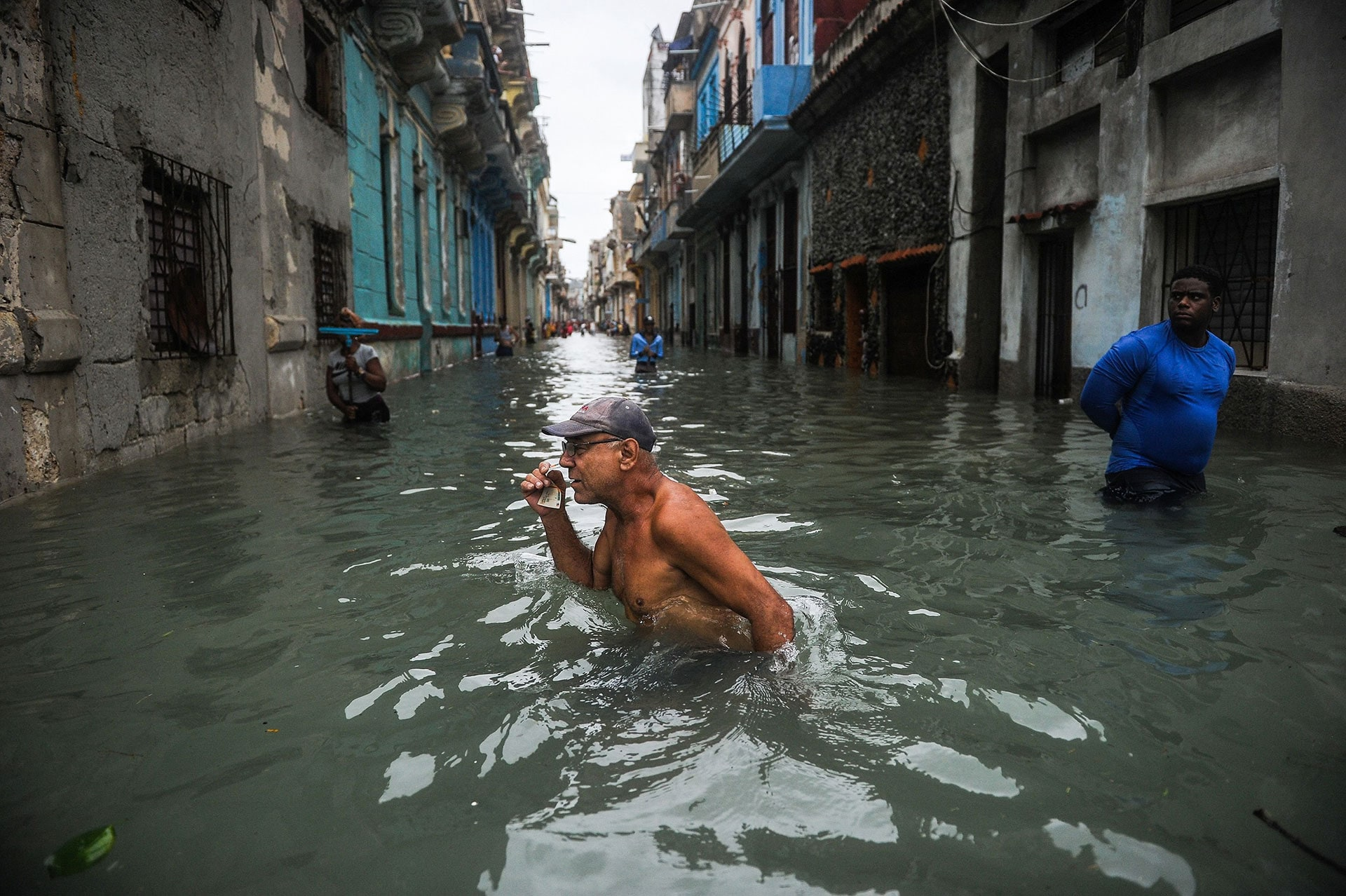 A Cuban man wades through a flooded street in Havana