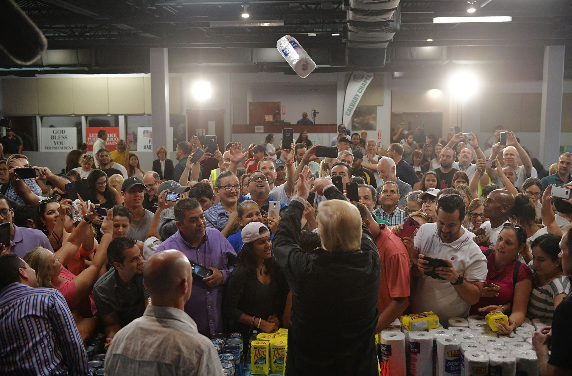 President Donald Trump tosses a roll of paper towels into a crowd