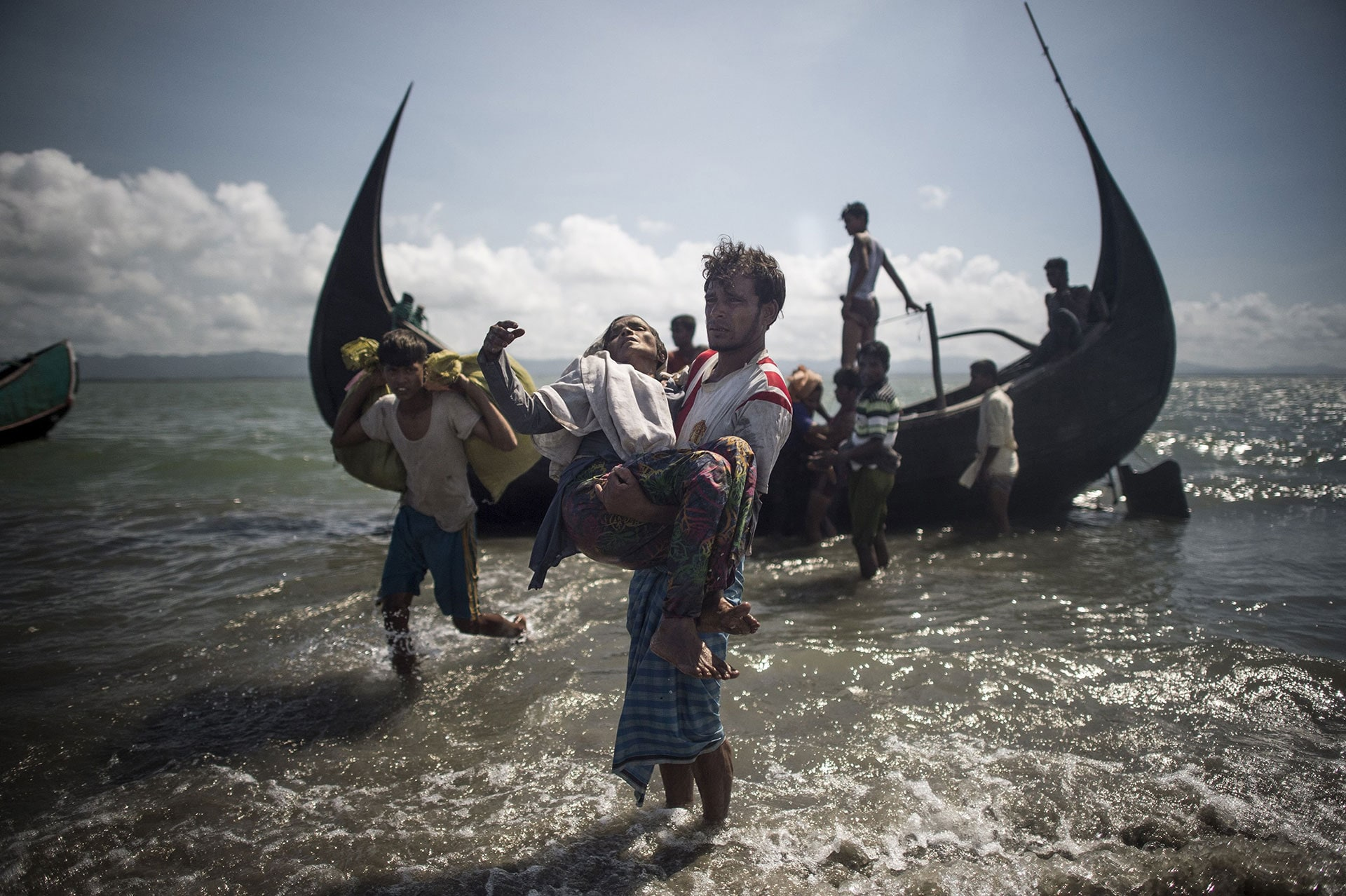 A Bangladeshi man helps Rohingya Muslim refugees
