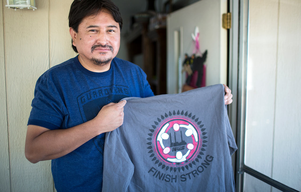 """""""I tell these guys they contribute every day,"""" said Jarvison Littlesunday, an NGS supervisor, with a shirt that encourages employees to stay on the job until the end. """"They provide the power, the power that makes monitors run in hospitals and lights go on in schools and air conditioning everywhere."""""""