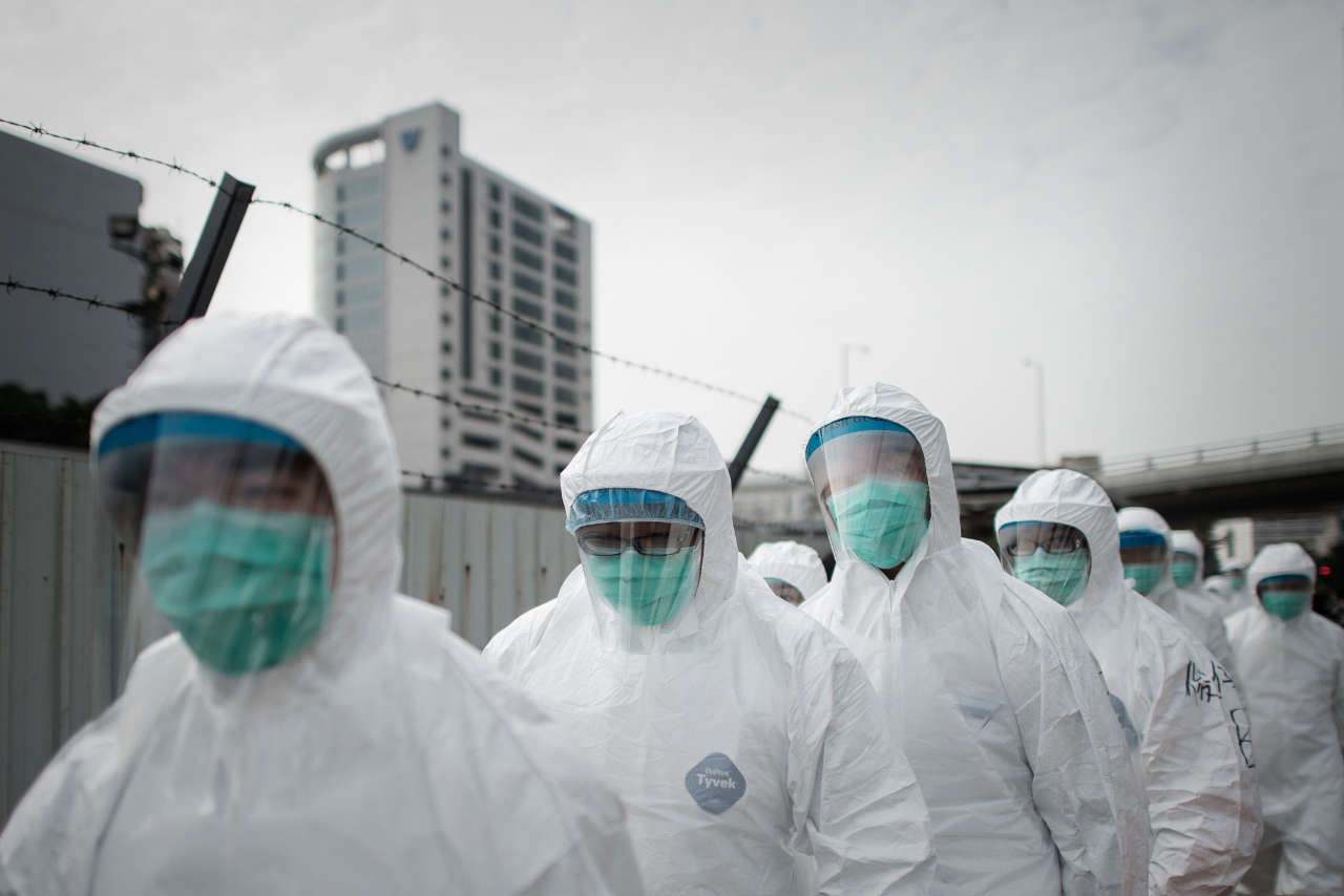 officials wearing masks and protective suits proceed to cull chickens in Hong Kong