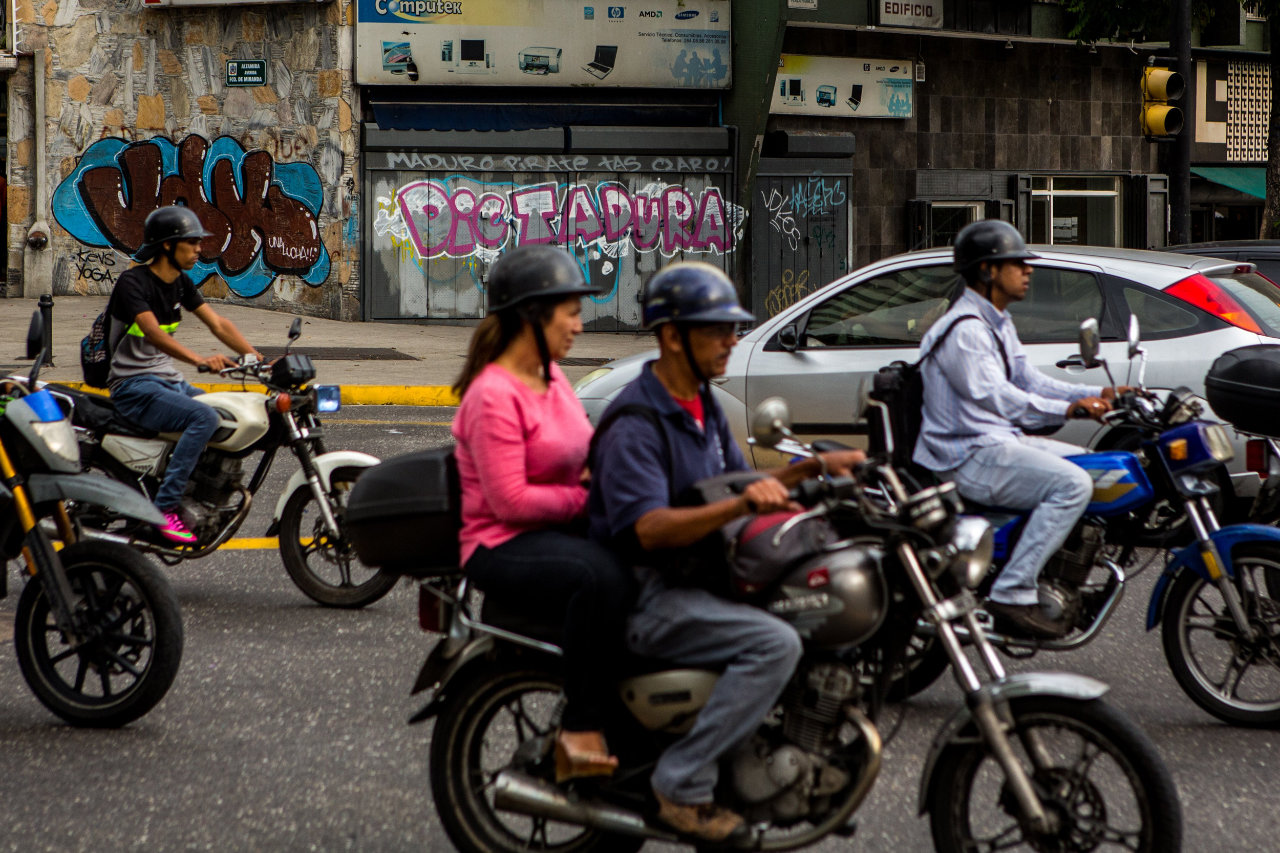 "Graffiti reading ""dictatorship"" covers a wall along Altamira's main road."