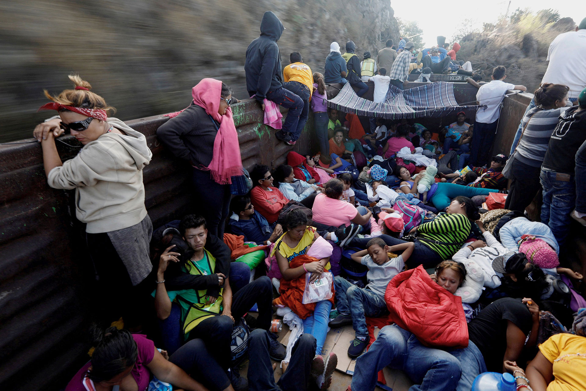 Central American migrants in the open wagon of a freight train