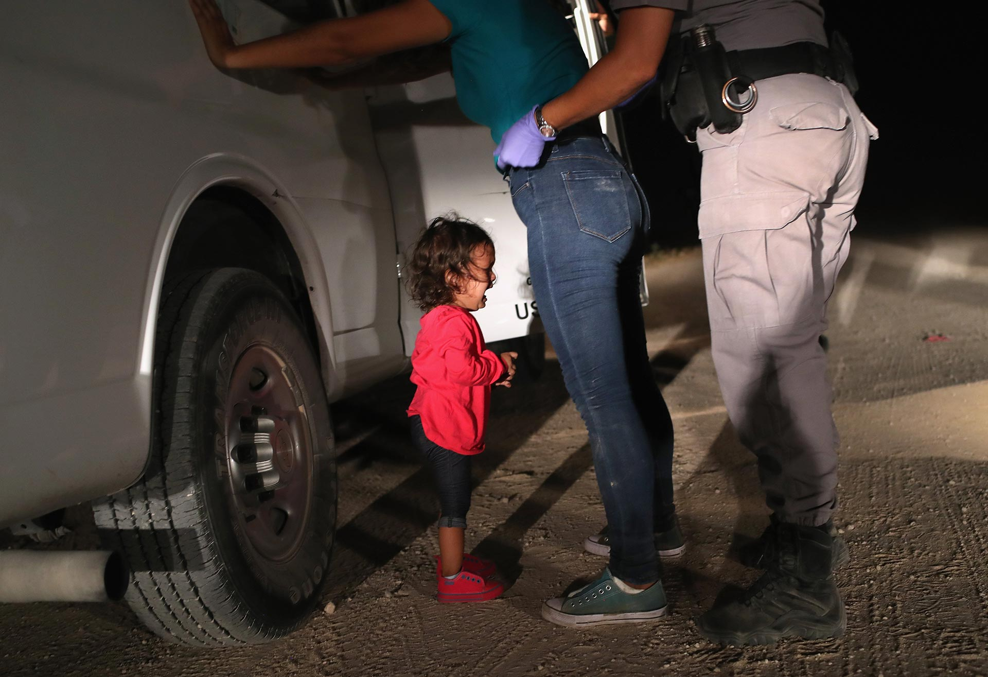 A 2-year-old girl cries as her mother is searched and detained near the U.S.-Mexico border