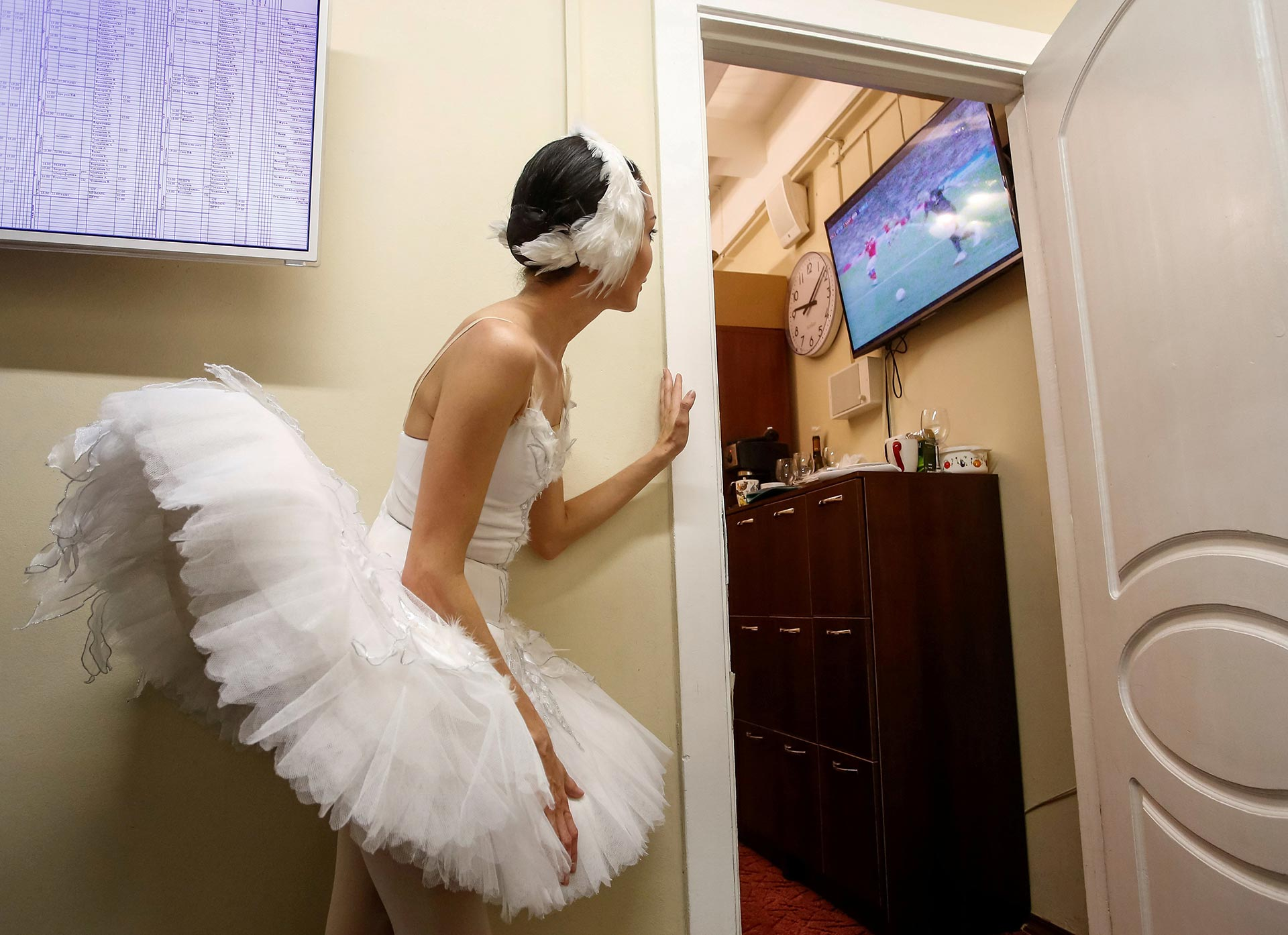 A ballerina watches the broadcast of the World Cup