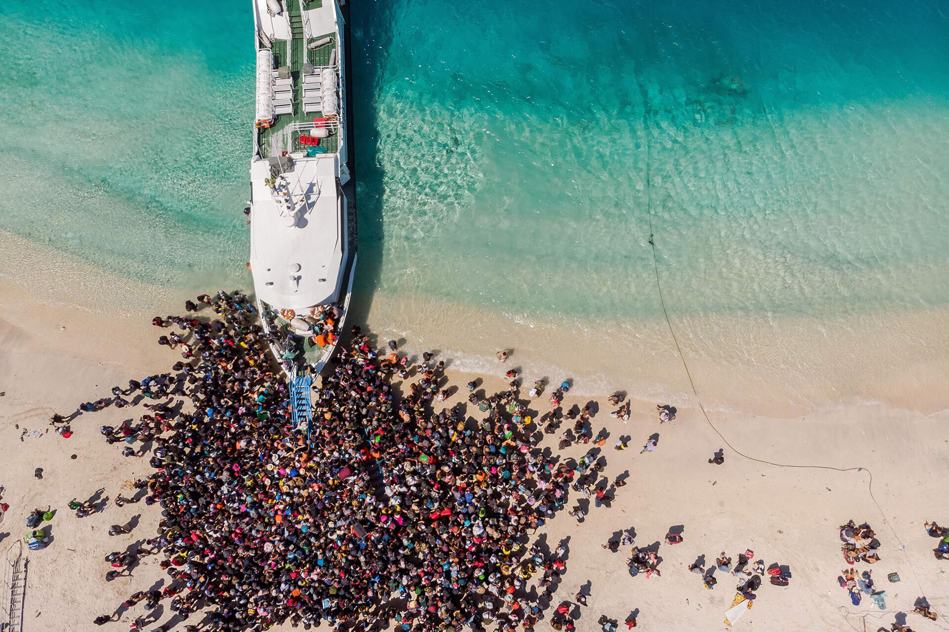 A crowd waits to be evacuated from Gili Trawangan island in Indonesia
