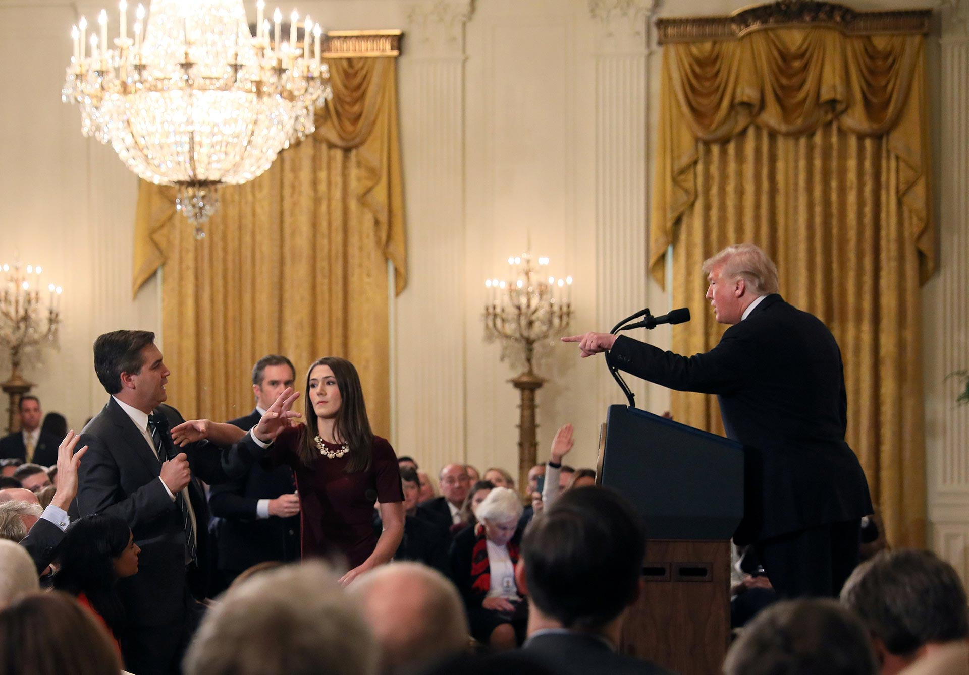 A White House intern reaches for the microphone held by CNN's Jim Acosta