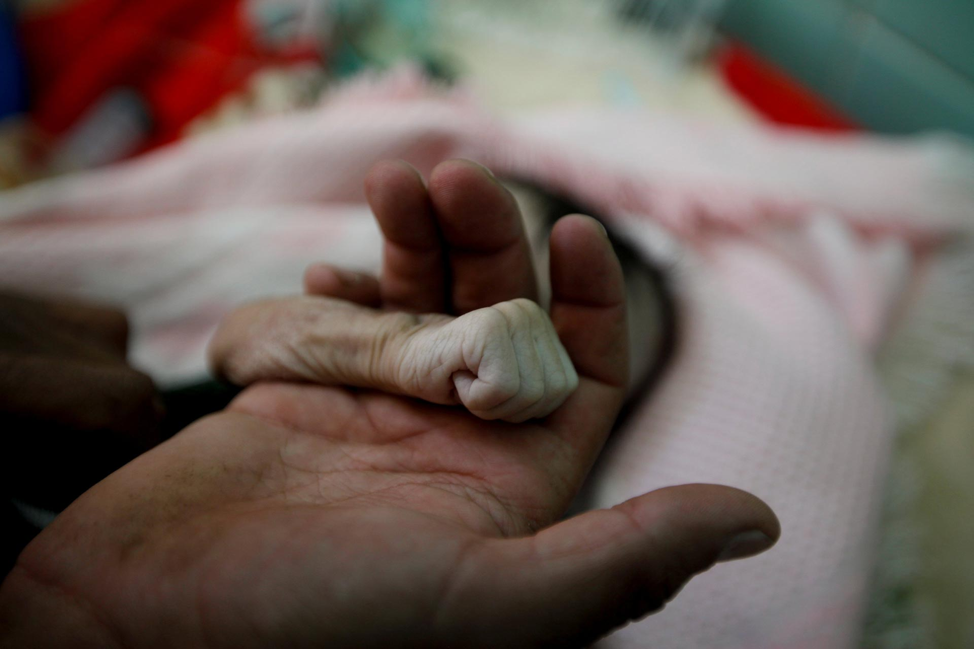 Saleh Hassan al-Faqeh holds the hand of his four-month-old daughter