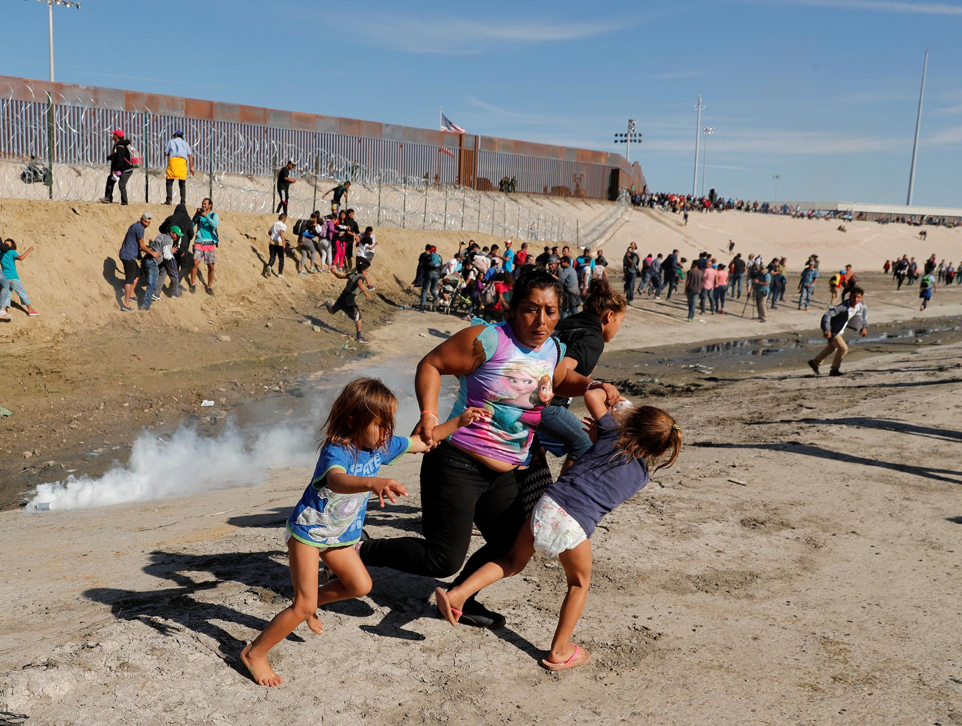 Maria Meza runs away from tear gas with her five-year-old twin daughters