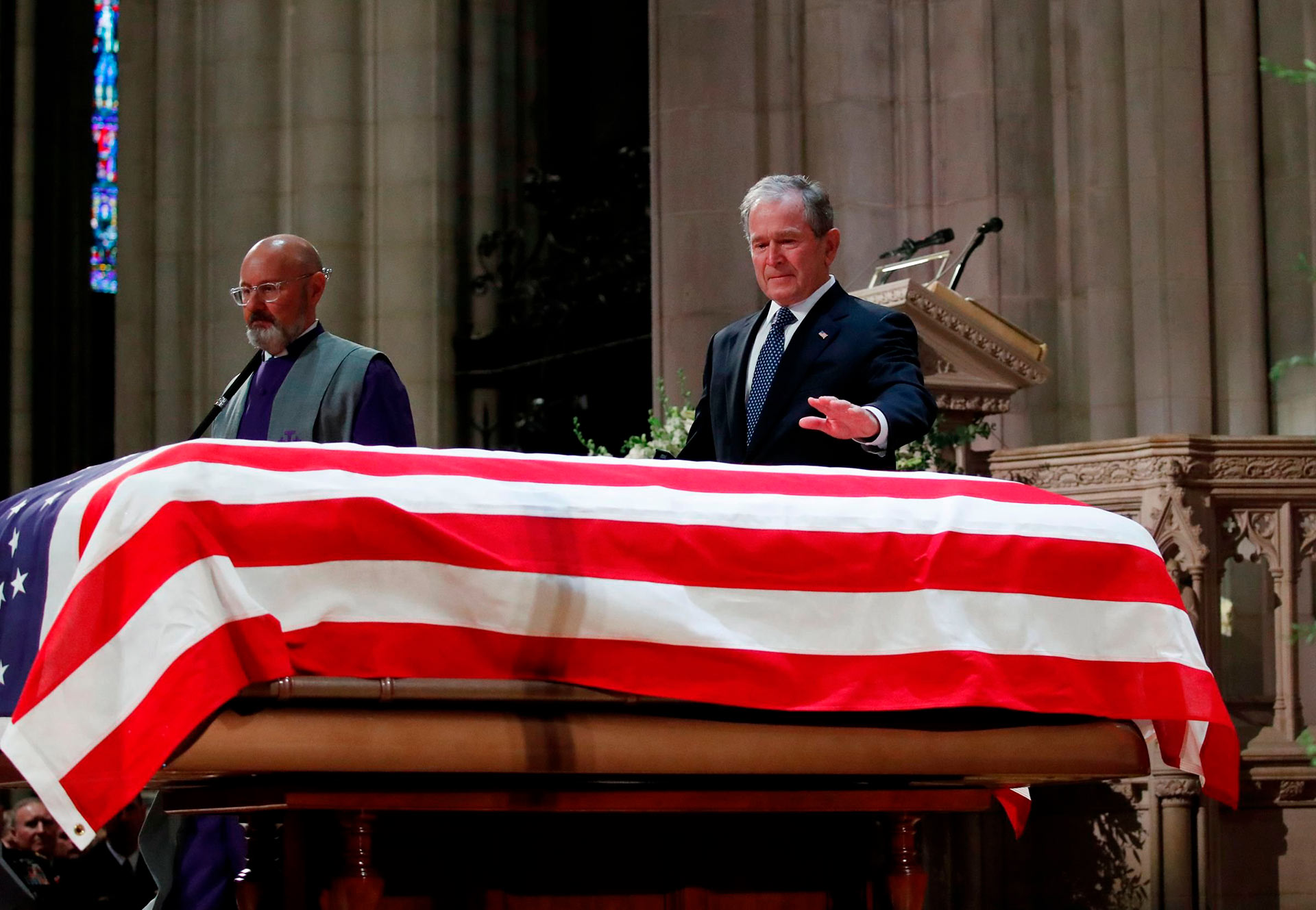 Former President George W. Bush touches the coffin after speaking at the funeral for his father