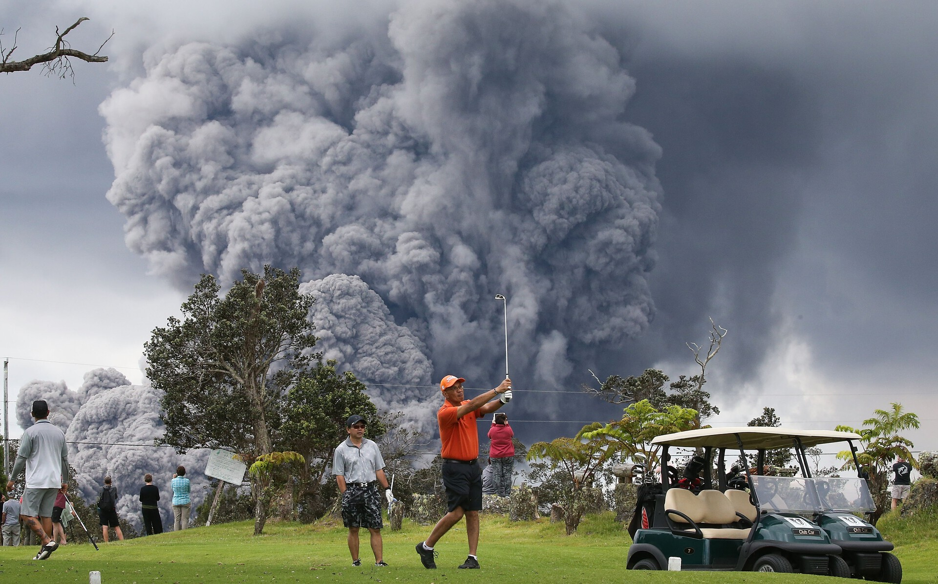 An ash plume from the Kilauea volcano rises in the distance behind golfers.