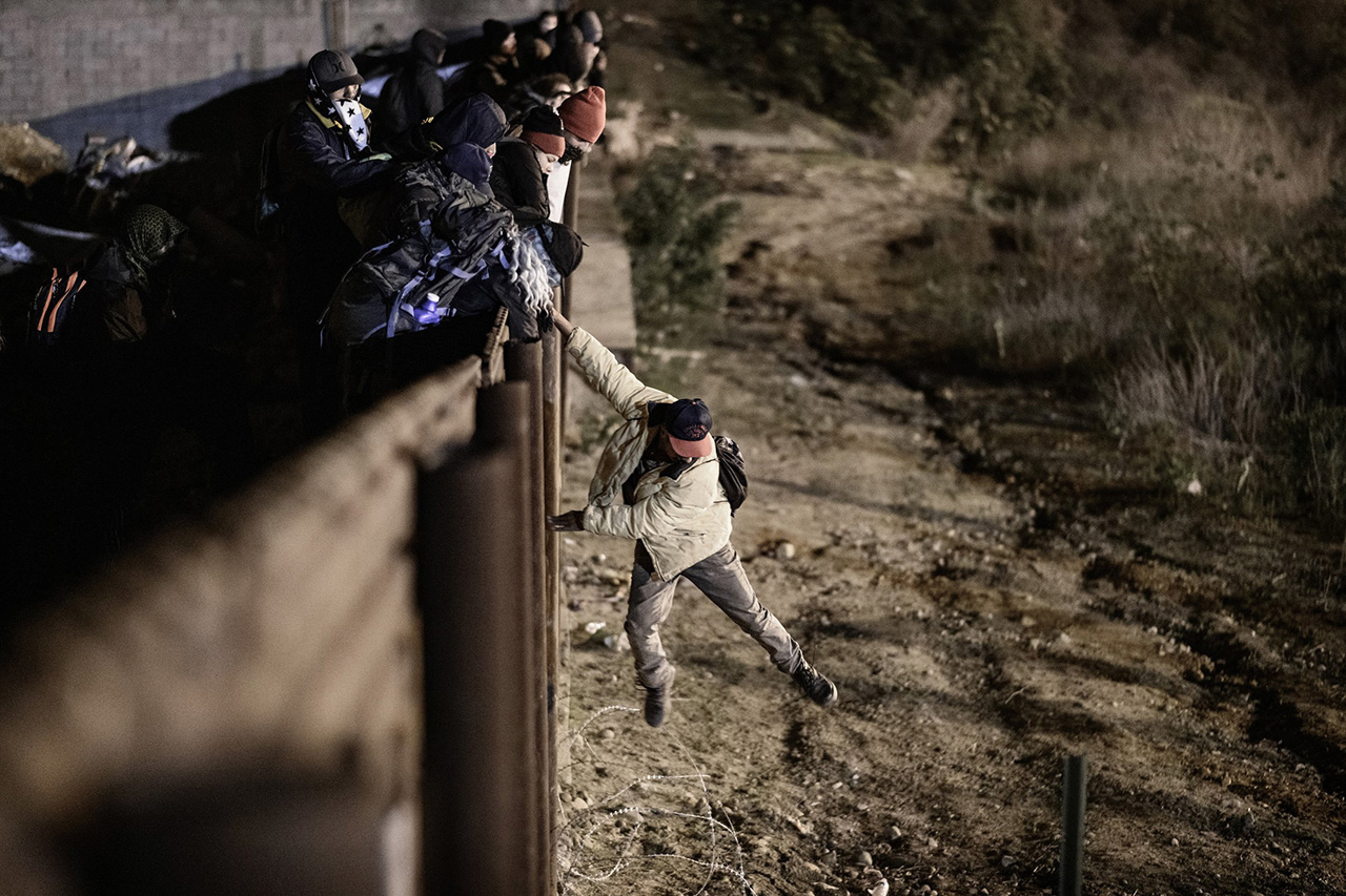 A migrant jumps from the border fence into the U.S. from Tijuana, Mexico, early on Jan. 1.