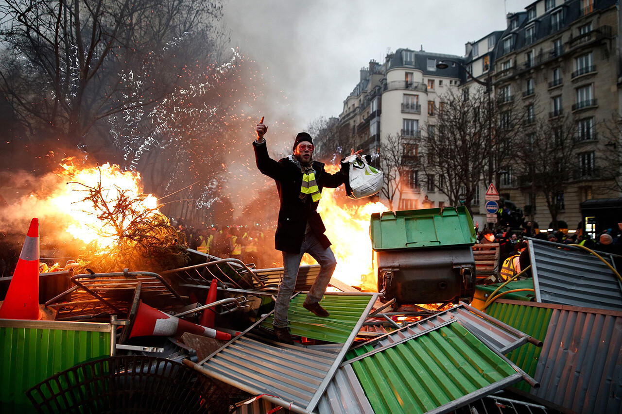 "A ""yellow vest"" demonstrator stands on a burning barricade in Paris on Jan. 5."