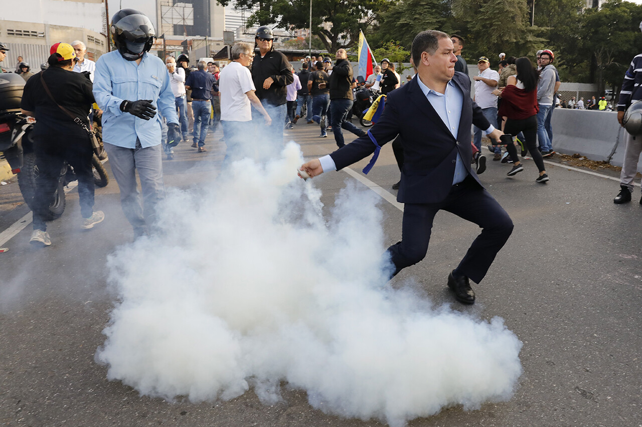 An opponent of Venezuelan President Nicolás Maduro returns a tear gas canister to soldiers who launched it.