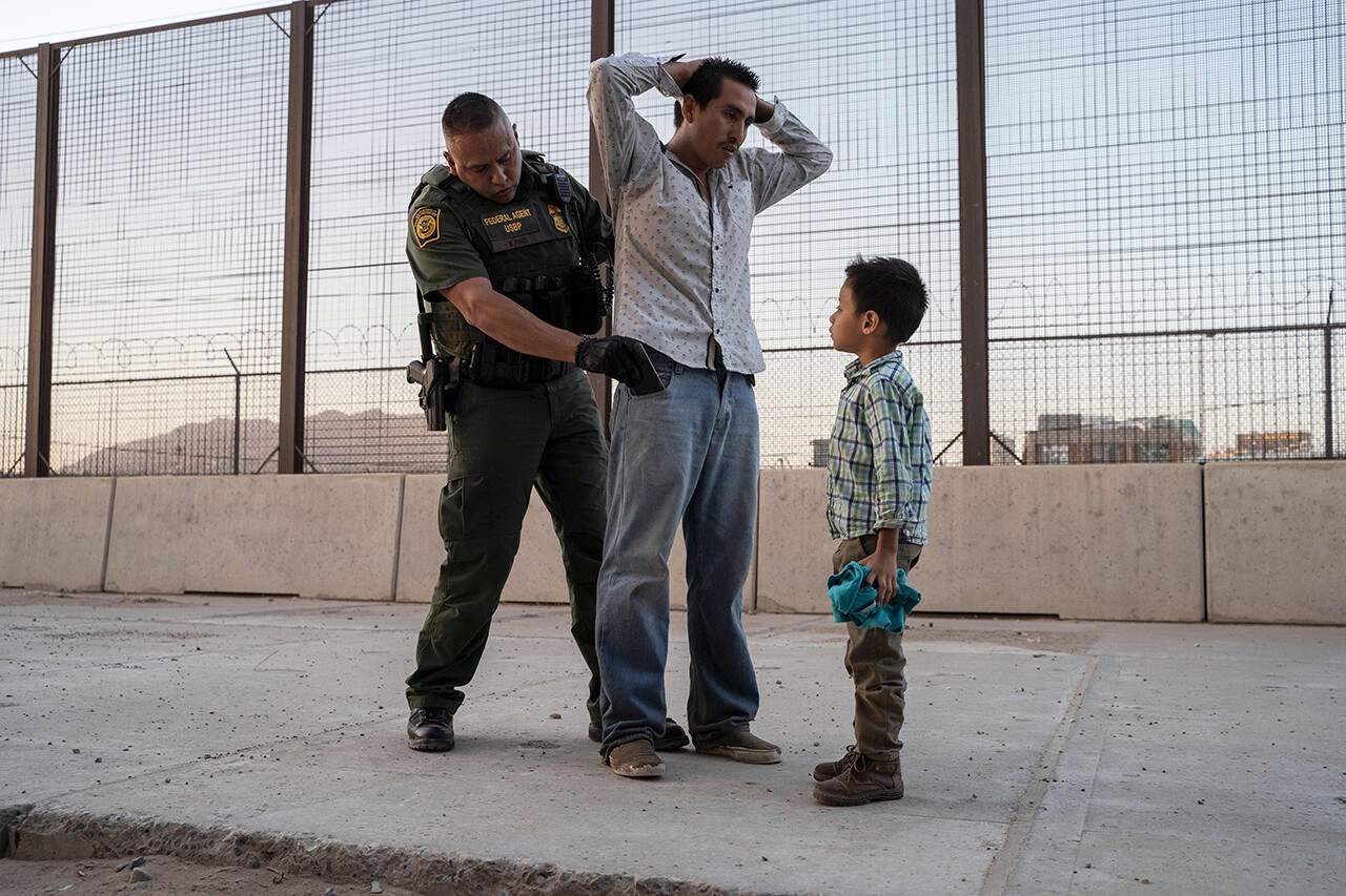 U.S. Customs and Border Protection Agent Frank Pino searches José, 27, as his 6-year-old son José Daniel watches in El Paso, Texas.