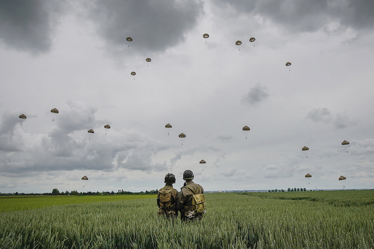 Military re-enactors look on as 280 paratroopers take part in a parachute drop onto fields on June 5 in Sannerville, France.