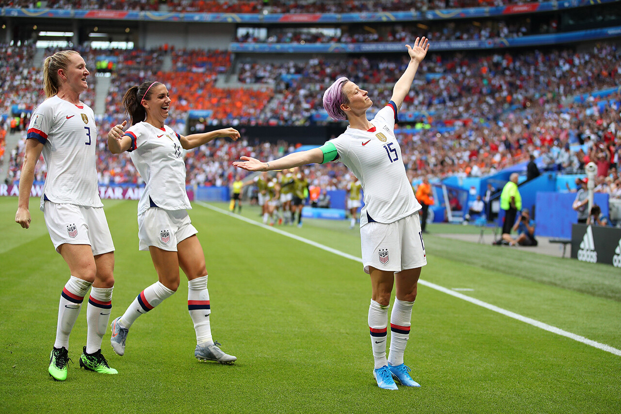 Megan Rapinoe strikes her signature pose as she celebrates with teammates Alex Morgan and Samantha Mewis.