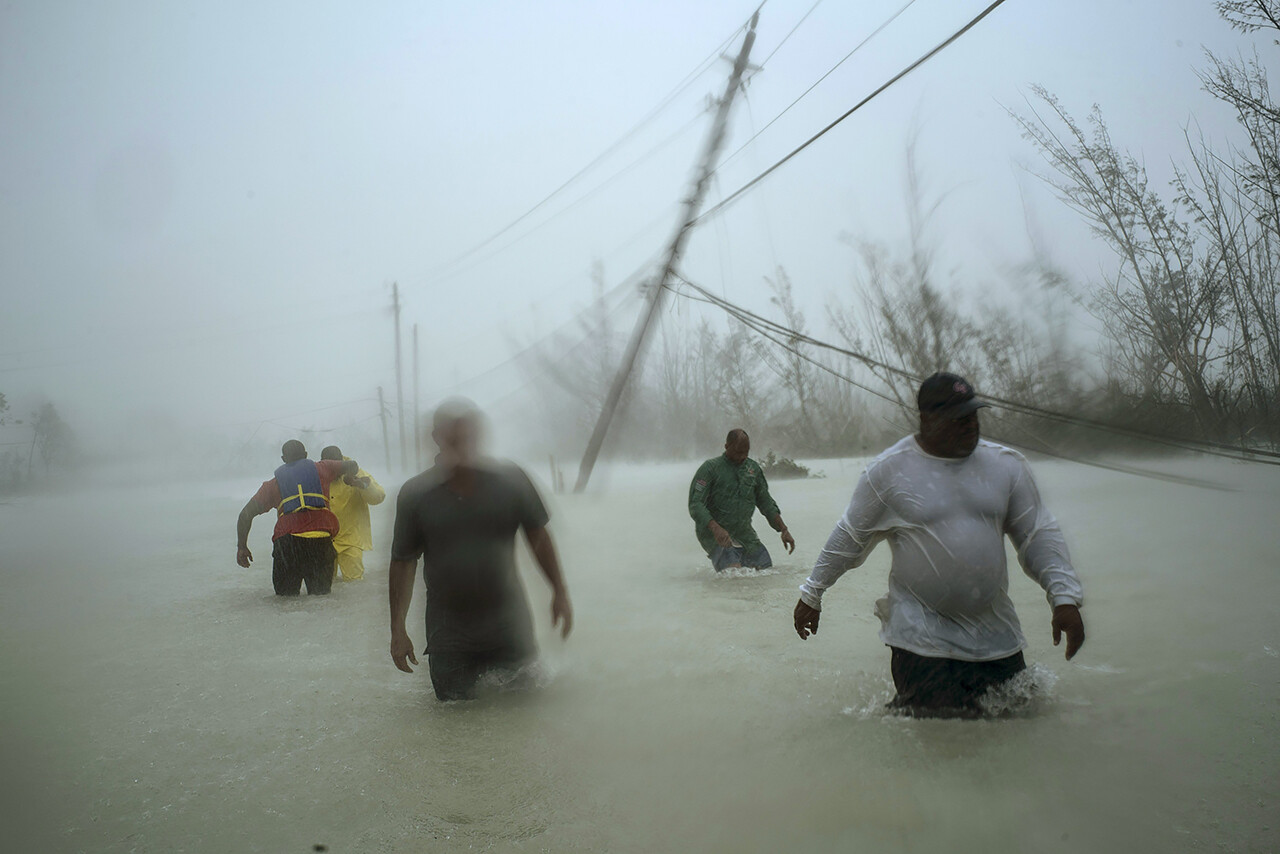 Volunteers walk through wind and rain from Hurricane Dorian as they rescue families in Freeport, Bahamas.