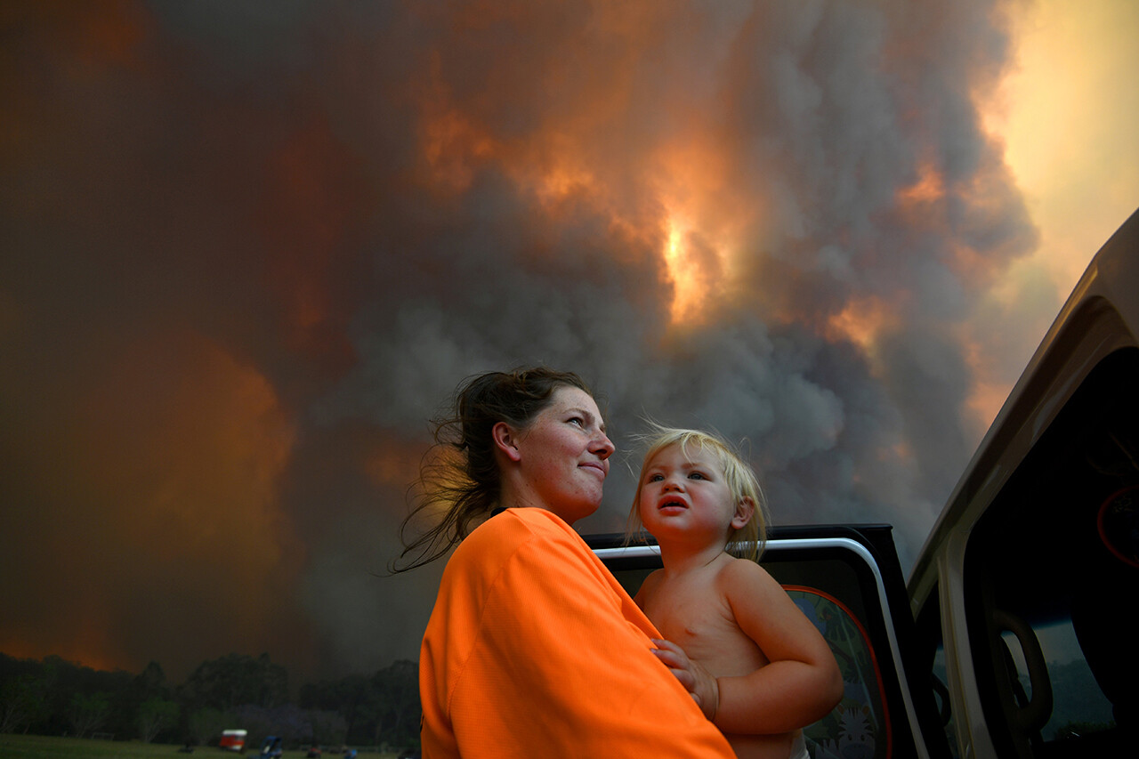 Sharnie Moren and her 18-month-old daughter, Charlotte, watch as thick smoke rises from bush fires near Nana Glen, Australia.