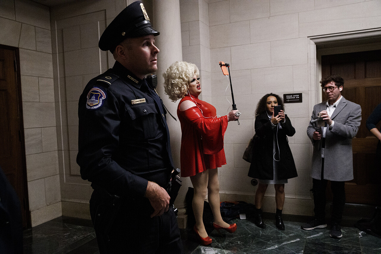 Pissi Myles, a drag performer from Asbury Park, N.J., and a special contributor with Happs News, reports with a cellphone during impeachment hearings.