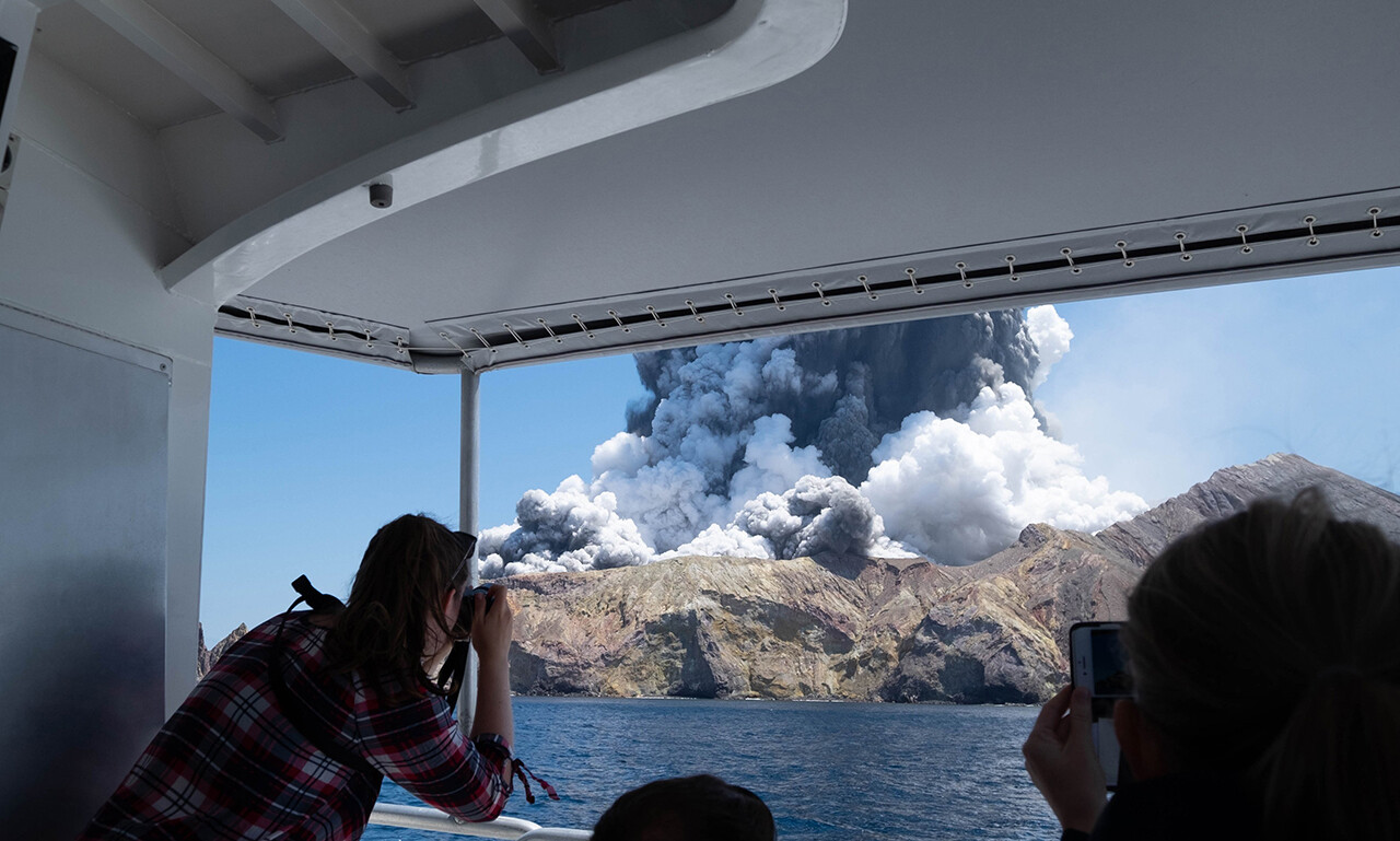 Tourists on a boat watch the eruption of the volcano on New Zealand's White Island.