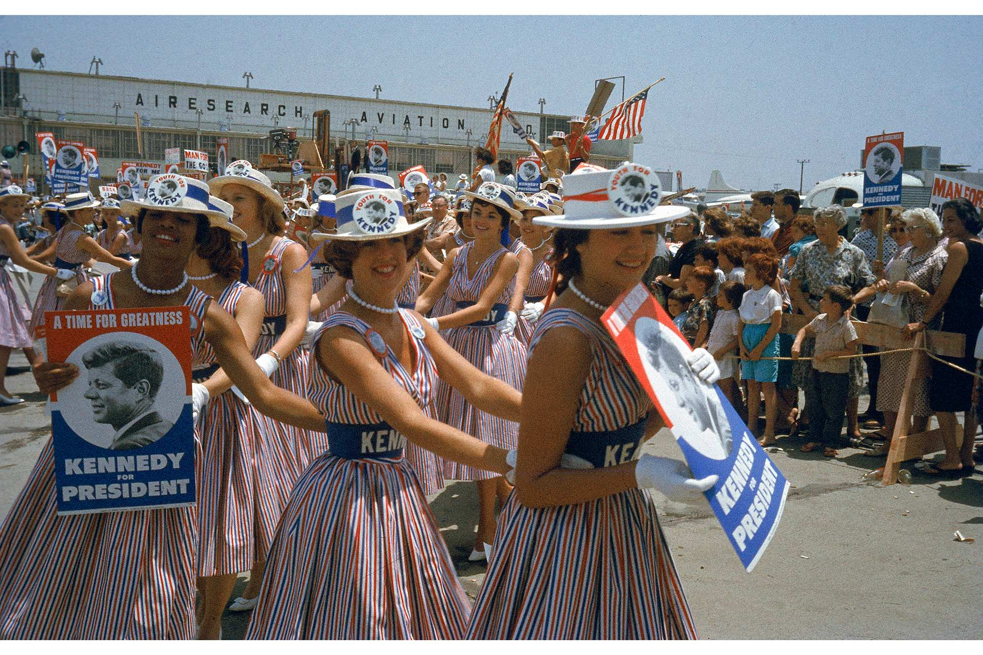 A group of young women at Los Angeles Airport wear matching red, white, and blue striped dresses and hold placards that read 'A Time for Greatness: Kennedy for President' as they await the arrival of presidential hopeful Senator John Kennedy, in town for the Democratic National Convention, Los Angeles, California, July 1960. | <span>Photo by Hank Walker/The LIFE Picture Collection/Getty Images</span>