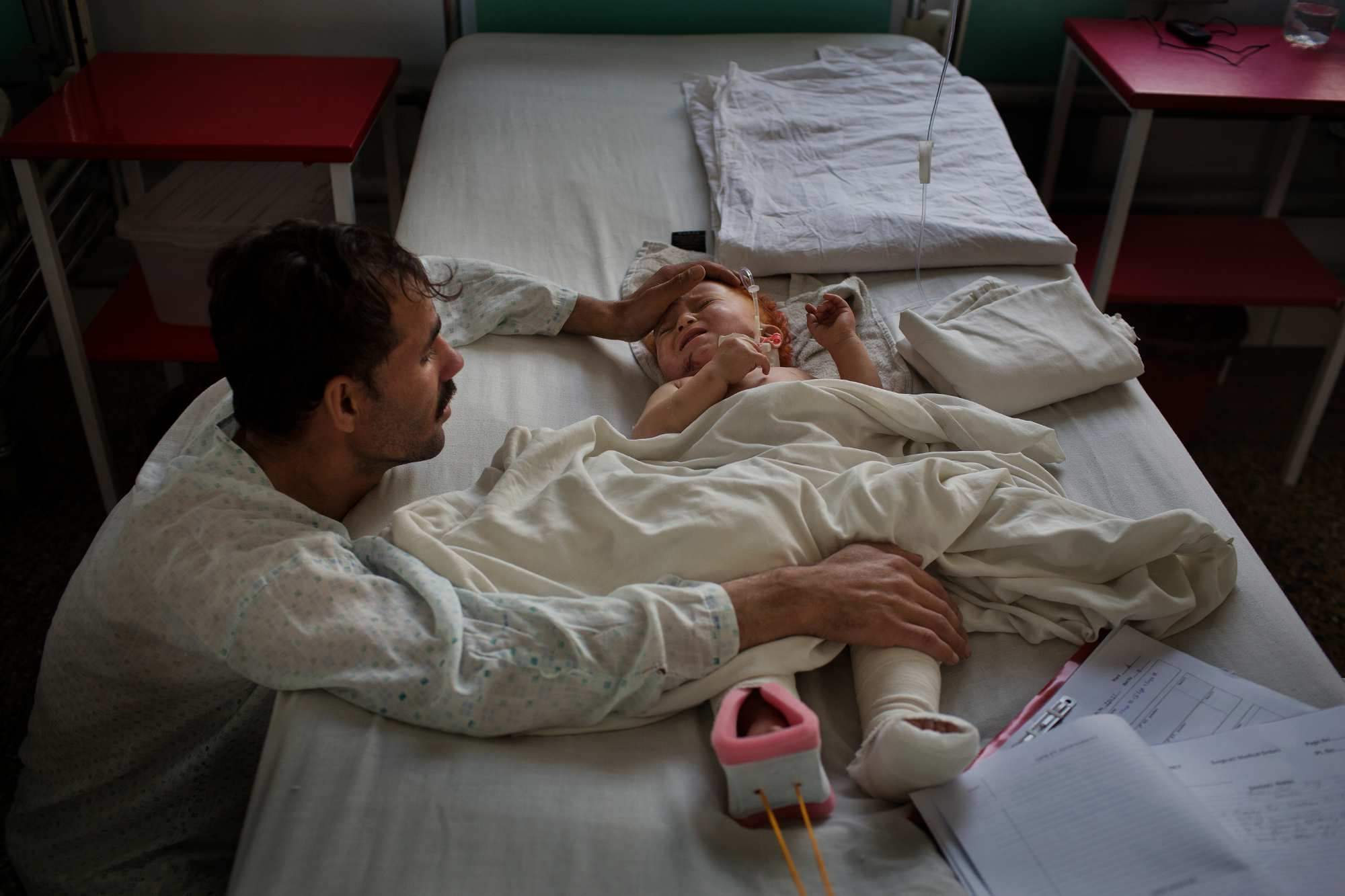 Abdullah, 8 months old, cries as his uncle comforts him. Abdullah came from Logar Province, where he was injured in a mine explosion that broke both of his legs and peppered him with shrapnel. His mother and father were killed in the blast.