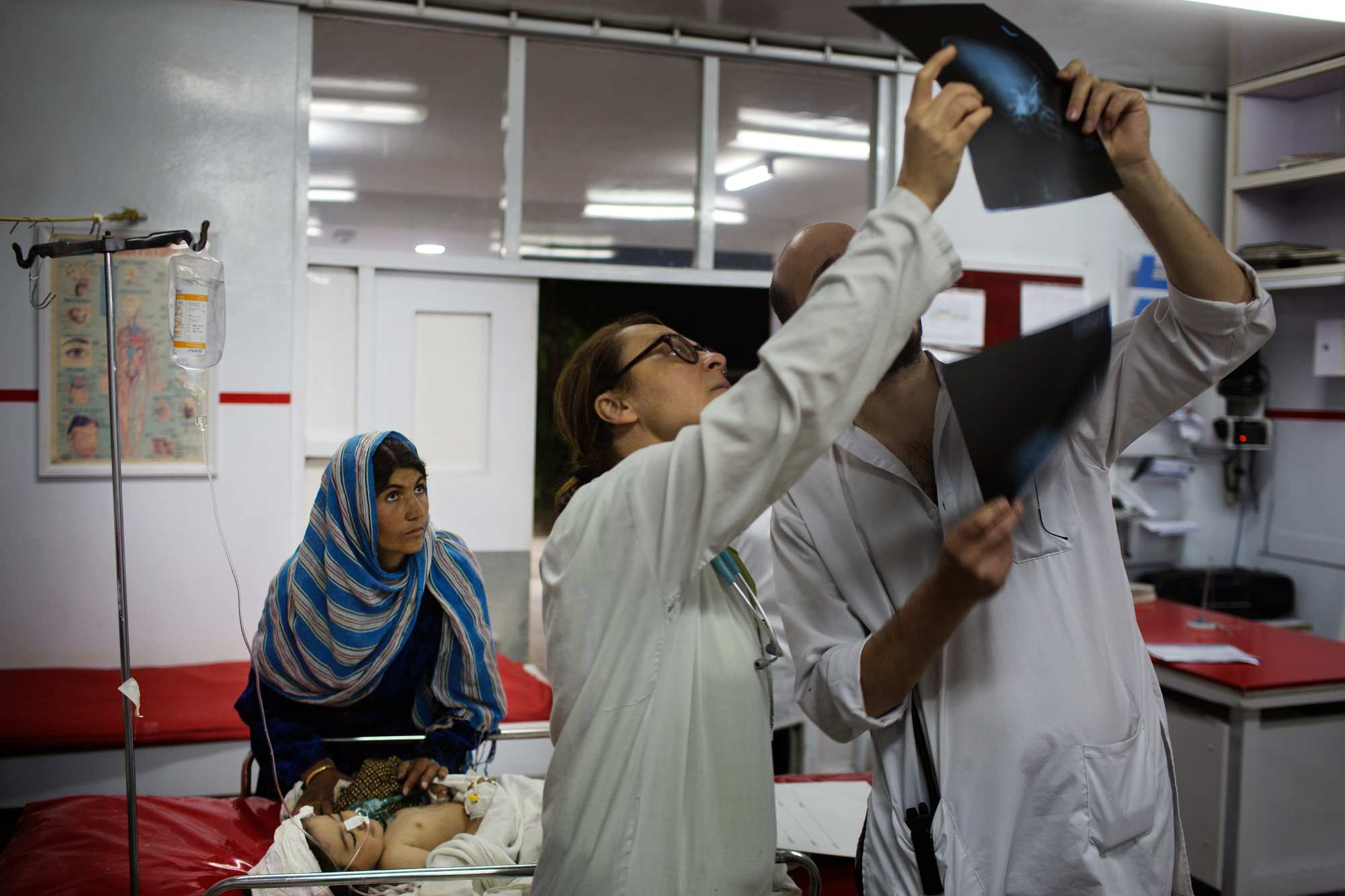 Dr. Daniele Scerrati, right, and a nurse look over the X-rays of 1 year-old Nasirullah who suffered a shrapnel injury to her head in Ghazni province, as her mother looks on.