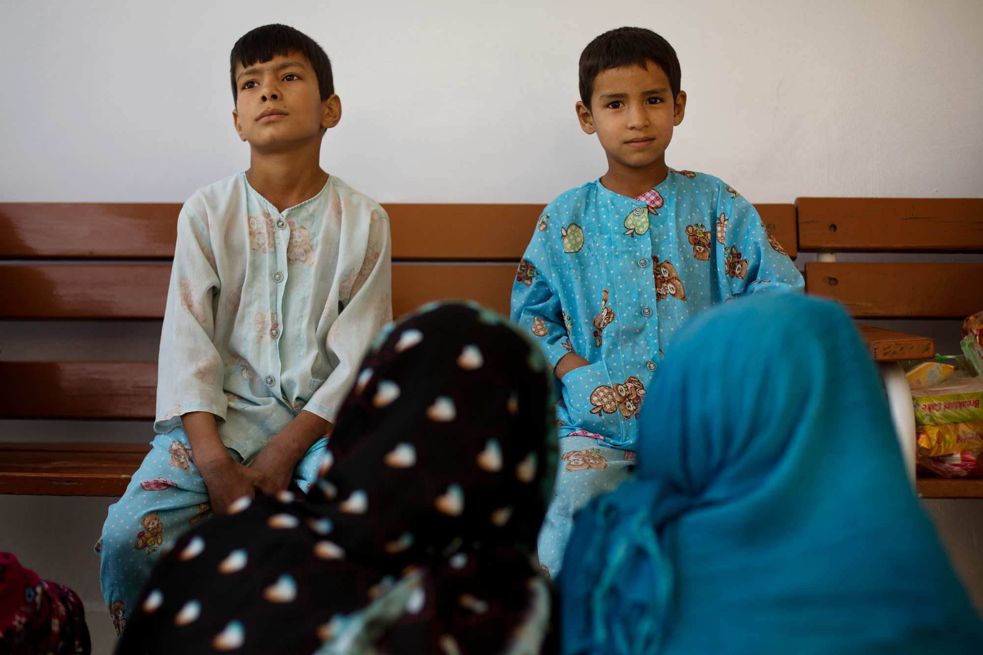 Jan Mohammed, 10, left, sits next to his brother Mirwais, 8, right, as they visit with family members at Emergency Surgical Center.