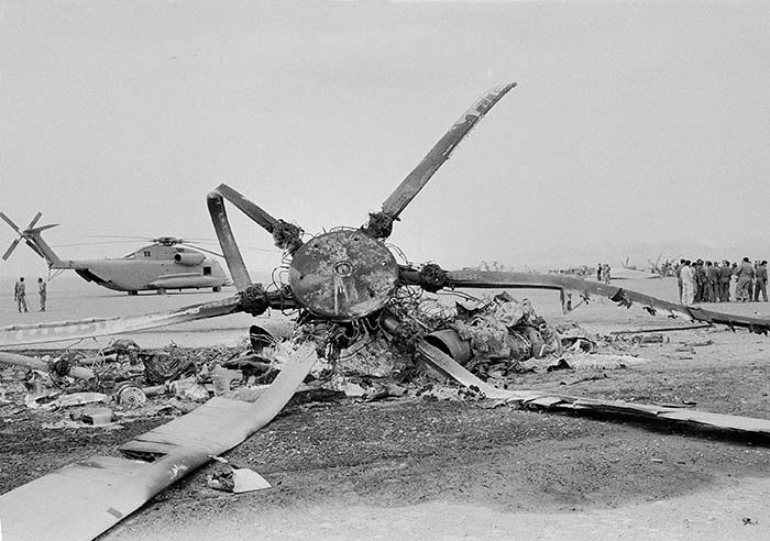 The rotor blades of a burned-out U.S. helicopter create a stark silhouette against the desert skies of eastern Iran, where the American commando mission to rescue the hostages proved impossible after equipment failure, seen April 27, 1980. In background is a U.S. helicopter that was also left behind when the mission was aborted.