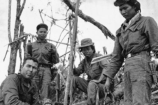 Captain Grimes talks with Laotian troops atop a hill captured from North Vietnamese.